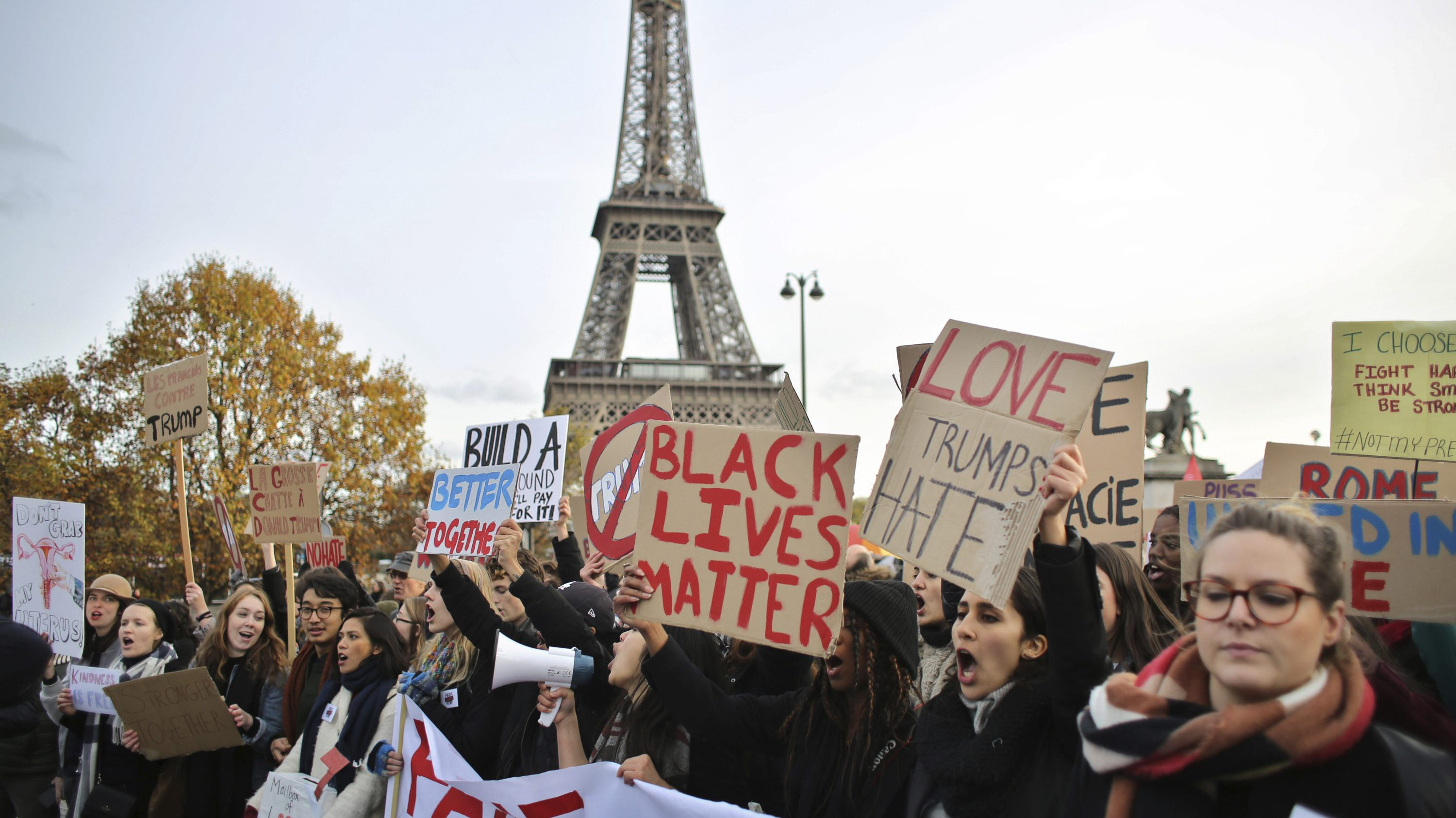 People hold banners and shout slogans against President-elect Donald Trump, in Paris, Saturday, Nov. 19, 2016. A few hundreds of critics of U.S. president-elect Donald Trump have marched through Paris to express concern about his respect for human rights, women and minorities.