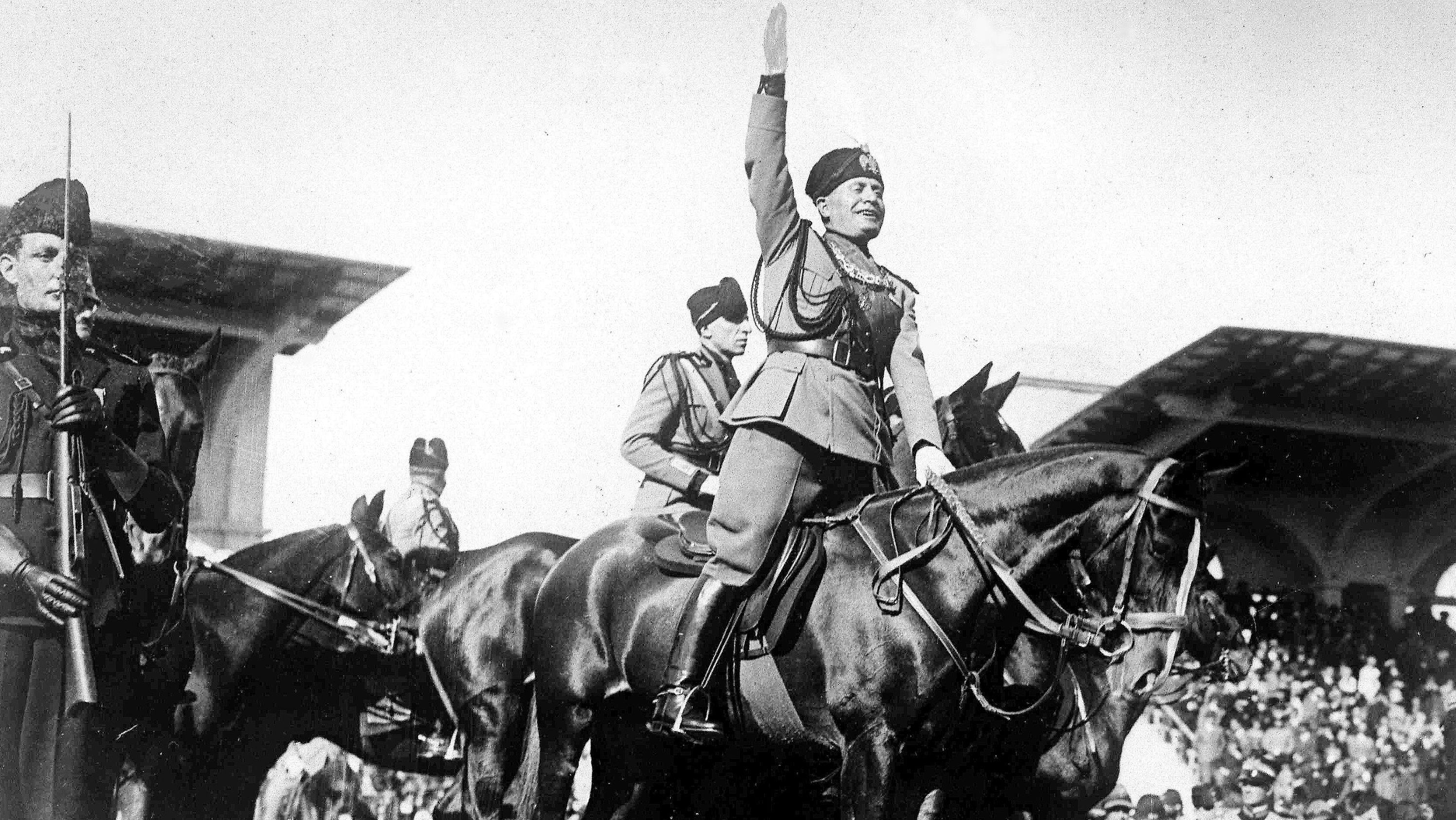 Italian dictator and Prime Minister Benito Mussolini, centre, on horseback salutes a review of fascists, somewhere in Italy, Oct. 1927. (AP Photo)