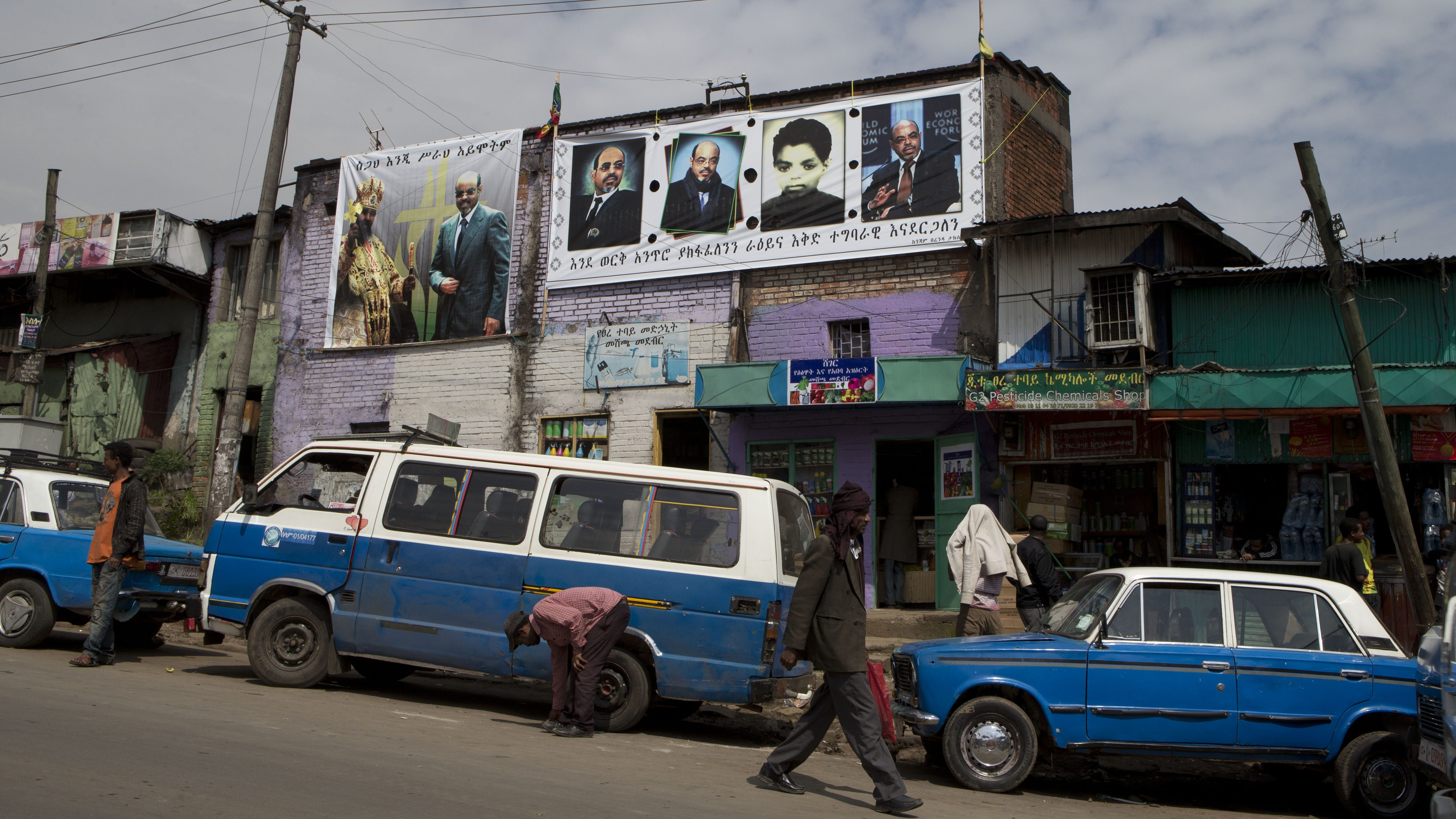 Taxis and a public transport minibus sit parked along an Addis Ababa street in 2012.