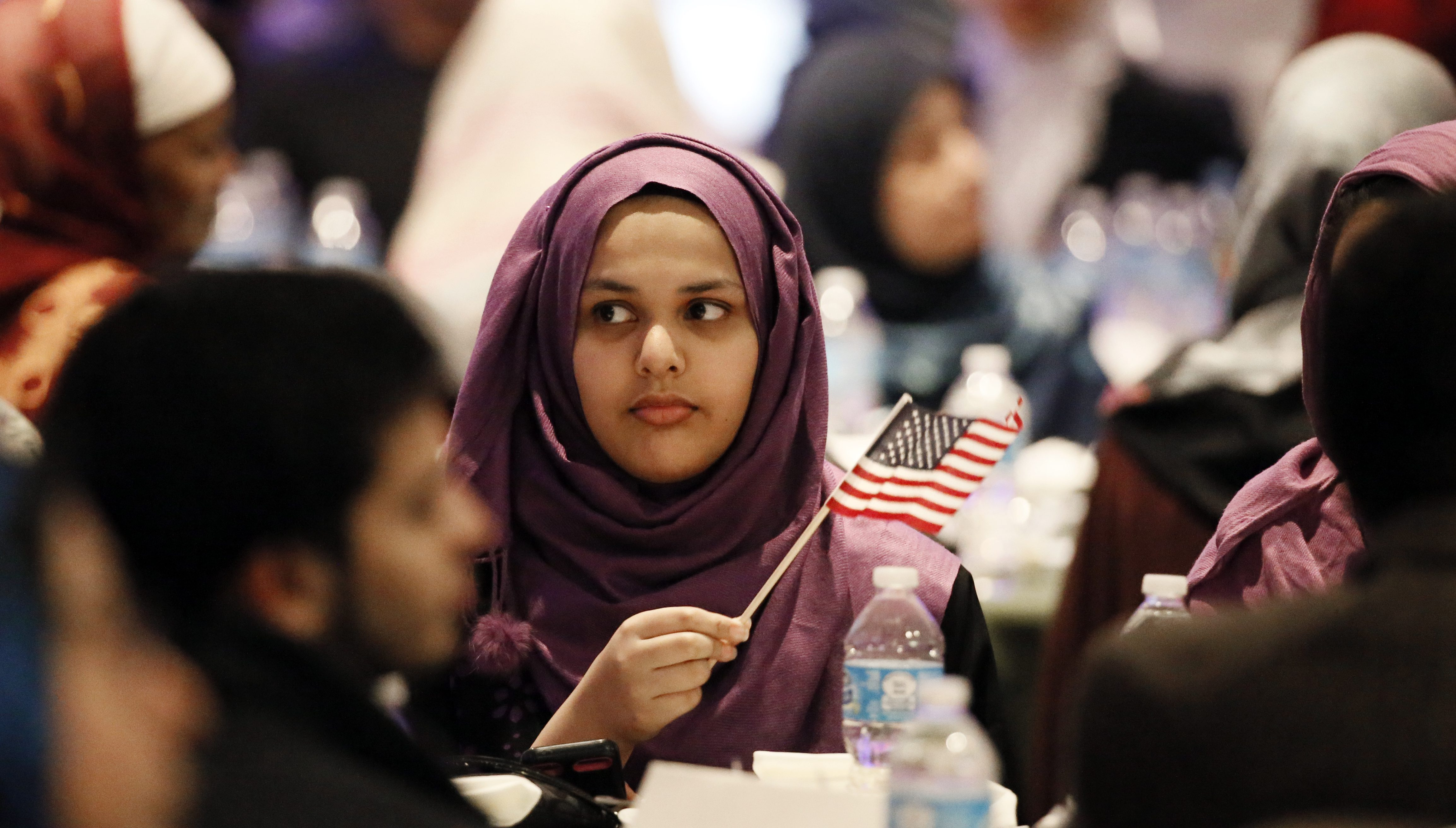 A young woman waves an American flag along with others at the beginning of a Muslim conference against terror and hate at the Curtis Culwell Center, Saturday, Jan. 17, 2015, in Garland, Texas.