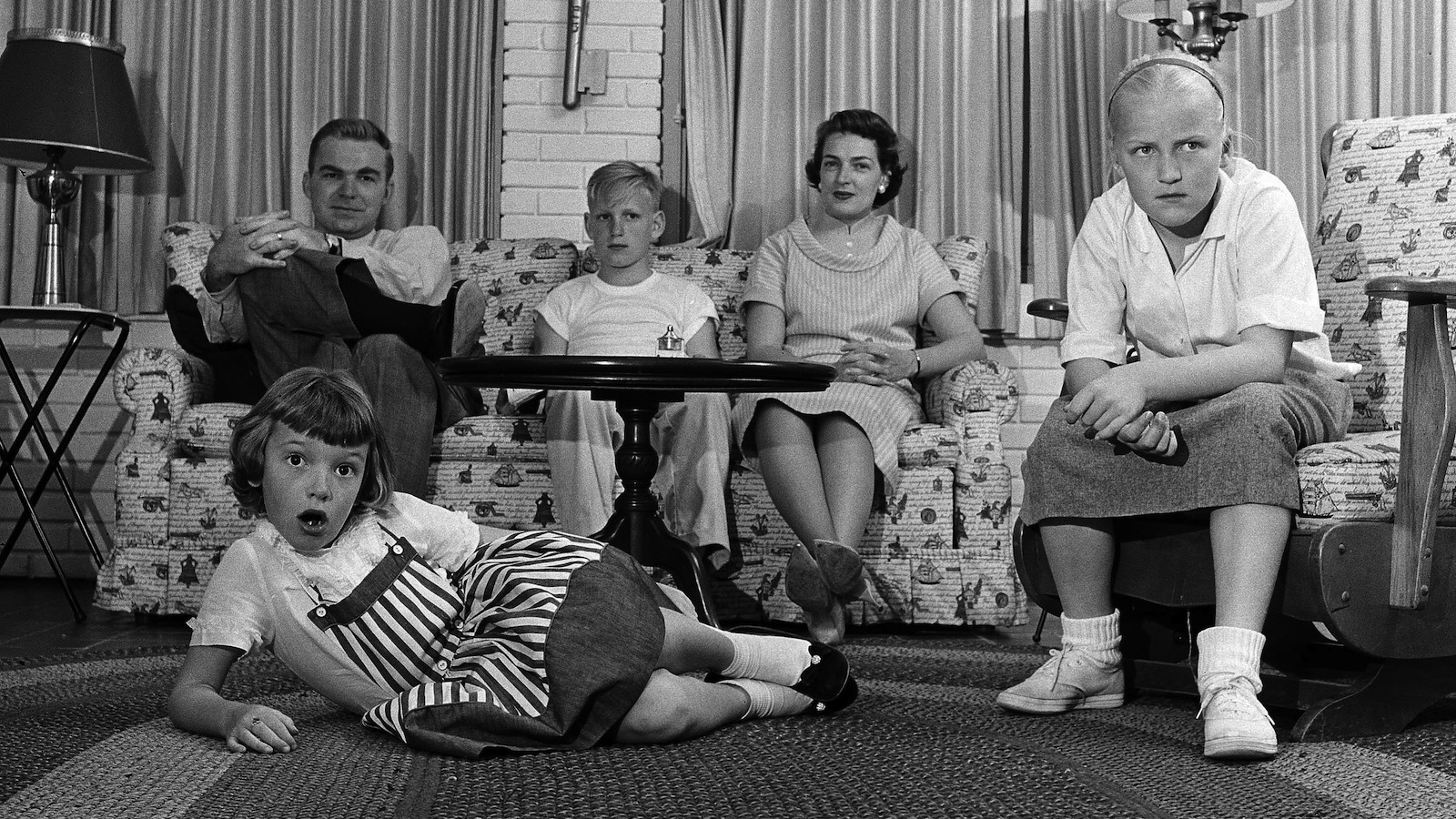 Like most other families, when Gov. J. Howard Edmondson, his wife and children have an evening together, they spend much of it before the television set, as seen May 30, 1959. On the couch in the background are the governor, son Jimmy, 11, and the governor's wife, Jeannette. Watching from the chair at right is daughter Jeanne, 9, and on the floor in her favorite TV-watching position of the youngest of the Edmondson, Patty, 7. (AP Photo)