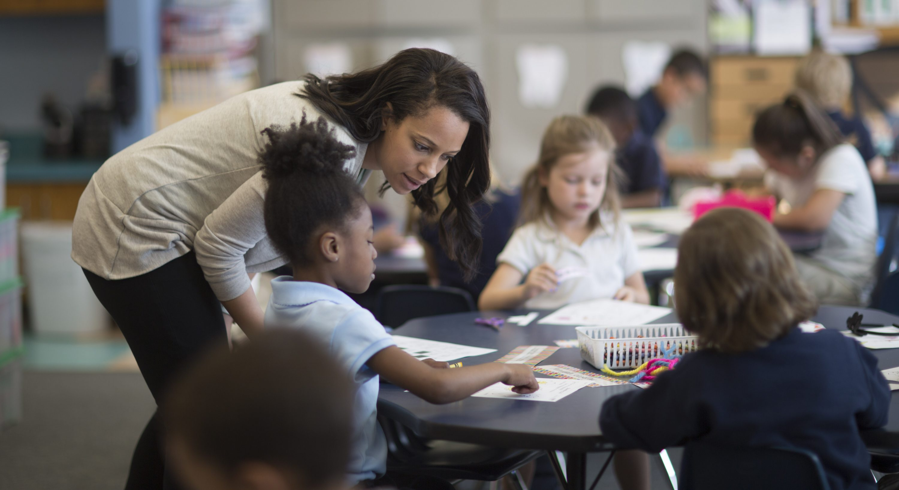 In this Monday, April 4, 2016 photo, Torie Shoecraft, who teaches kindergarten at Nichols Hills Elementary in Oklahoma City, works with her students on a class room assignment. Oklahoma educators and parents say the latest round of proposed funding cuts to schools could have devastating consequences for students, as the state suffers its worst-ever budget crisis. (AP Photo/J Pat Carter)