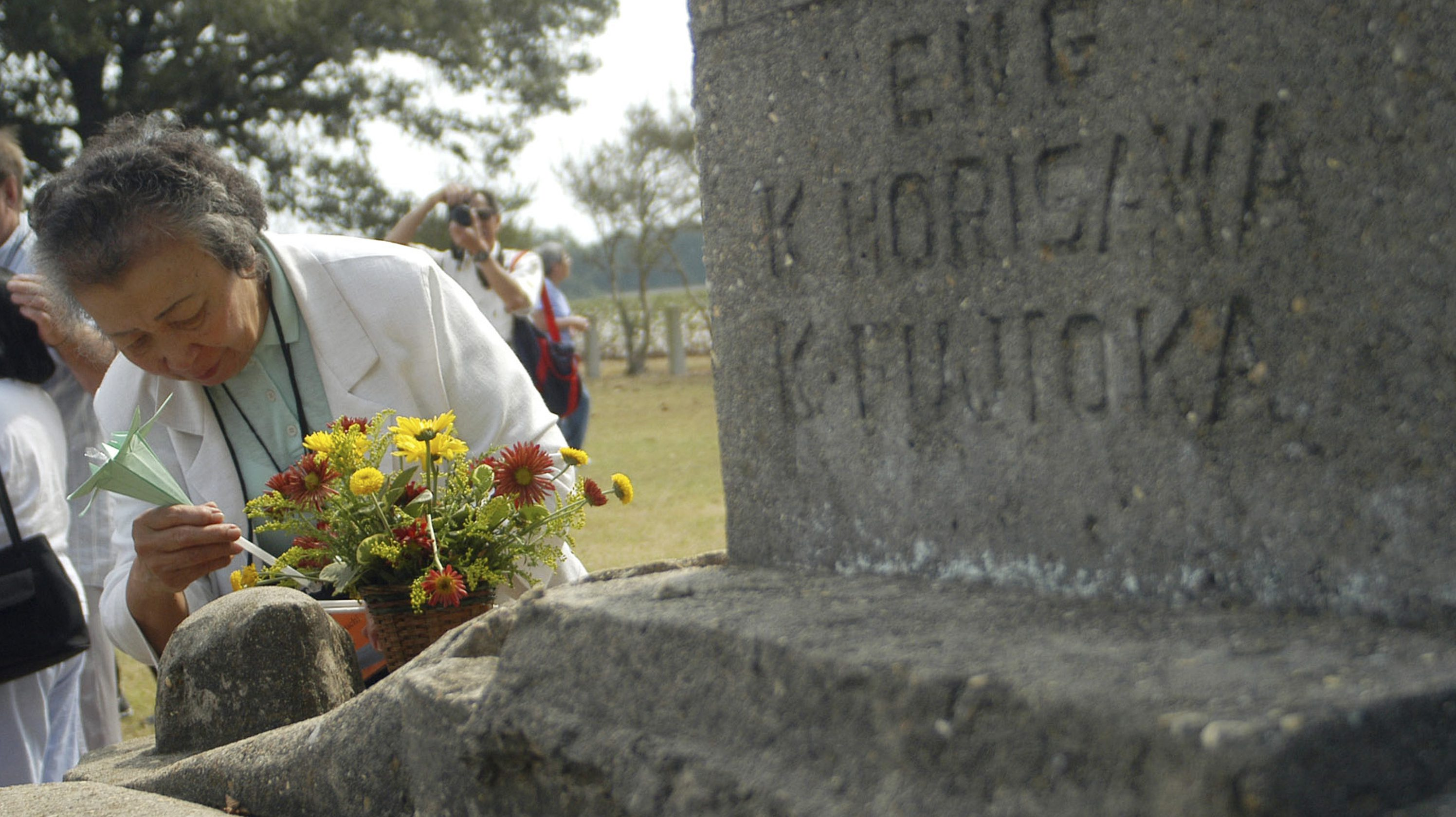 In this file photo taken Sept. 26, 2004, Nobu Sekiguchi of Pasadena, MD., decorates a flower arraignment with a handmade flower on a memorial  erected for the inhabitants of a Japanese-American World War II interment camp in Rohwer, Ark.