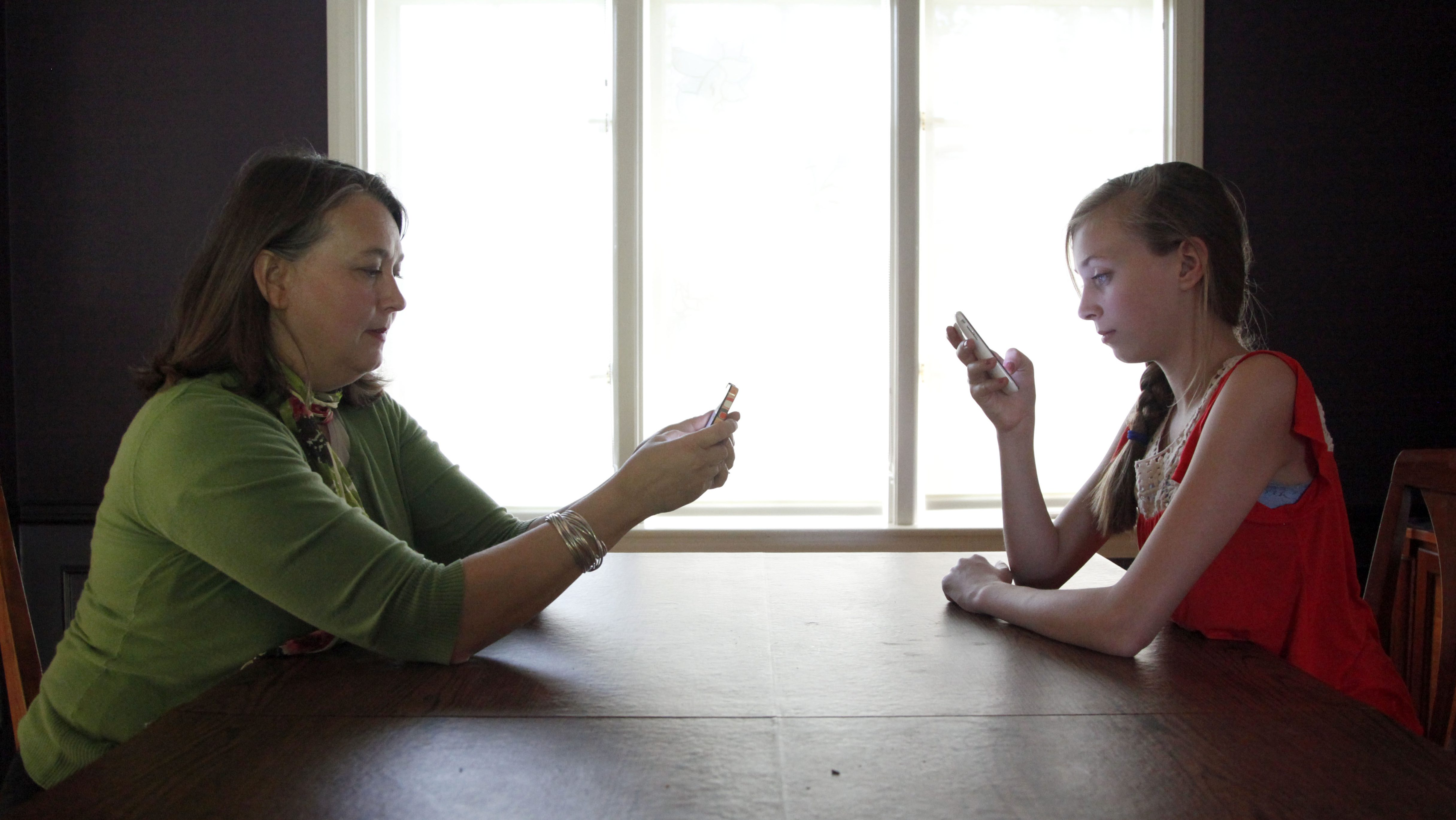 FILE -In this May 24, 2012 file photo, Anna Schiferl, right, and her mother, Joanna, pose for a photograph holding their cell phones in the dining room of their LaGrange, Ill. home. Statistics from the Pew Internet & American Life Project show that, these days, many people with cell phones prefer texting over a phone call. It's not always young people, though the data indicates that the younger you are, the more likely you are to prefer texting. But many experts say the most successful communicators will, of course, have the ability to do both talk or text, and know the most appropriate times to use those skills. (AP Photo/Charles Rex Arbogast, File)