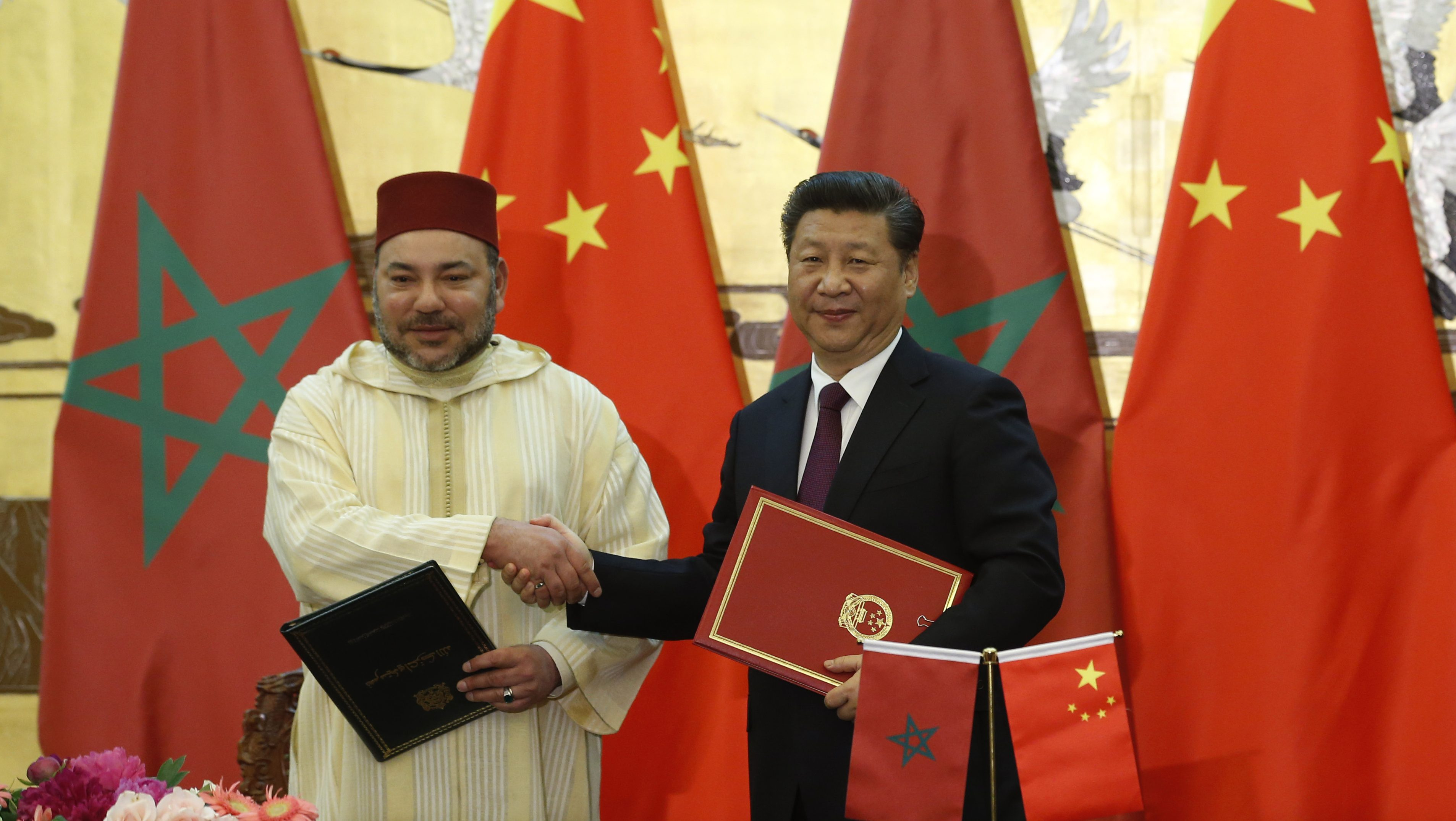 Chinese President Xi Jinping, right, and Moroccan King Mohammed VI pose for photographers as they shake hands after signing documents during a signing ceremony at the Great Hall of People in Beijing, China, Wednesday, May 11, 2016. (Kim Kyung-hoon/Pool Photo via AP)