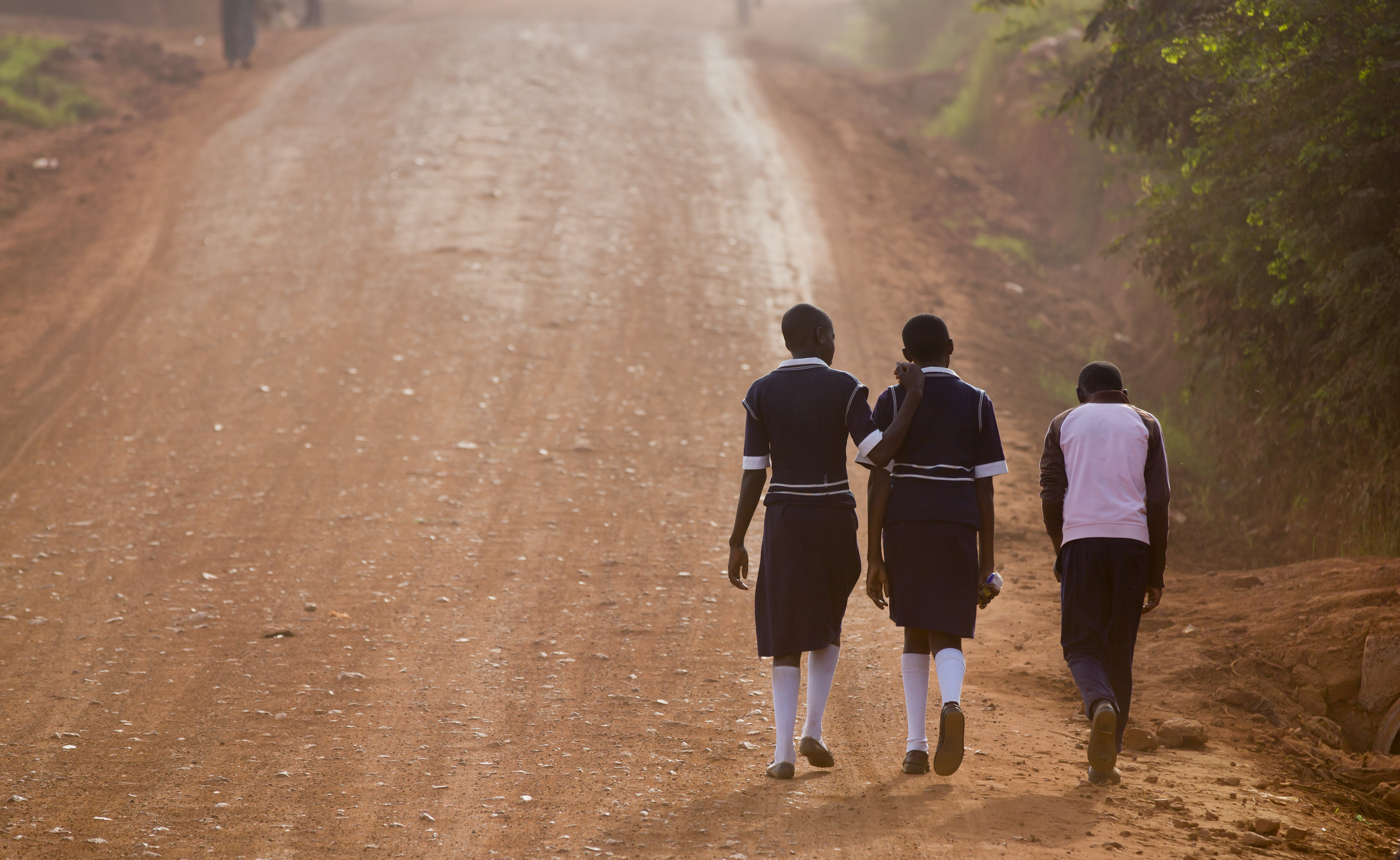 Ugandan children walk up a dusty murram road to school in the morning on the first day of the new term, in Kasangati, near Kampala, in Uganda Monday, Feb. 22, 2016. The new term started later than usual due to the recent presidential elections.