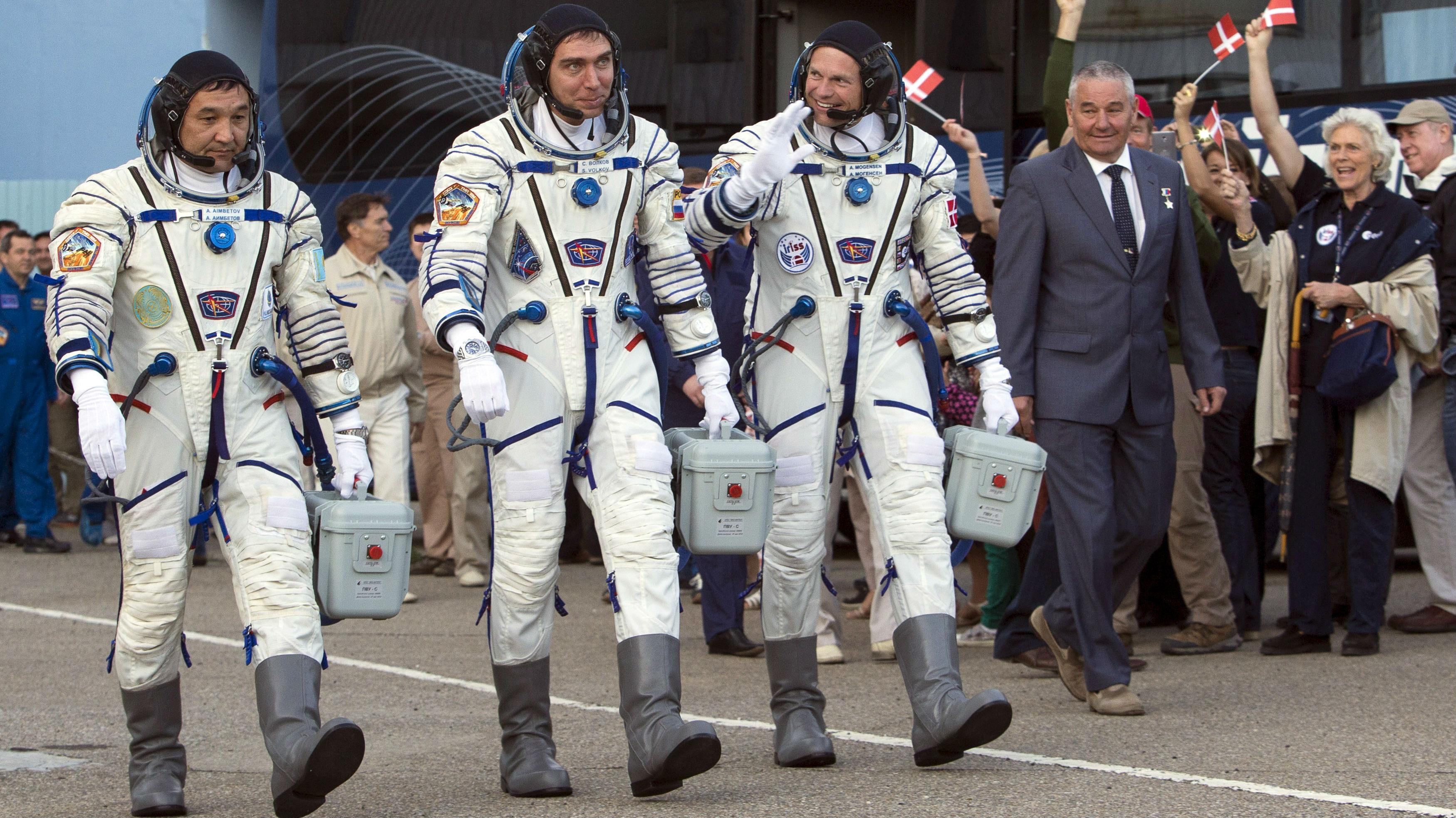 Three astronauts from Kazakstan walk in their spacesuits in Denmark.