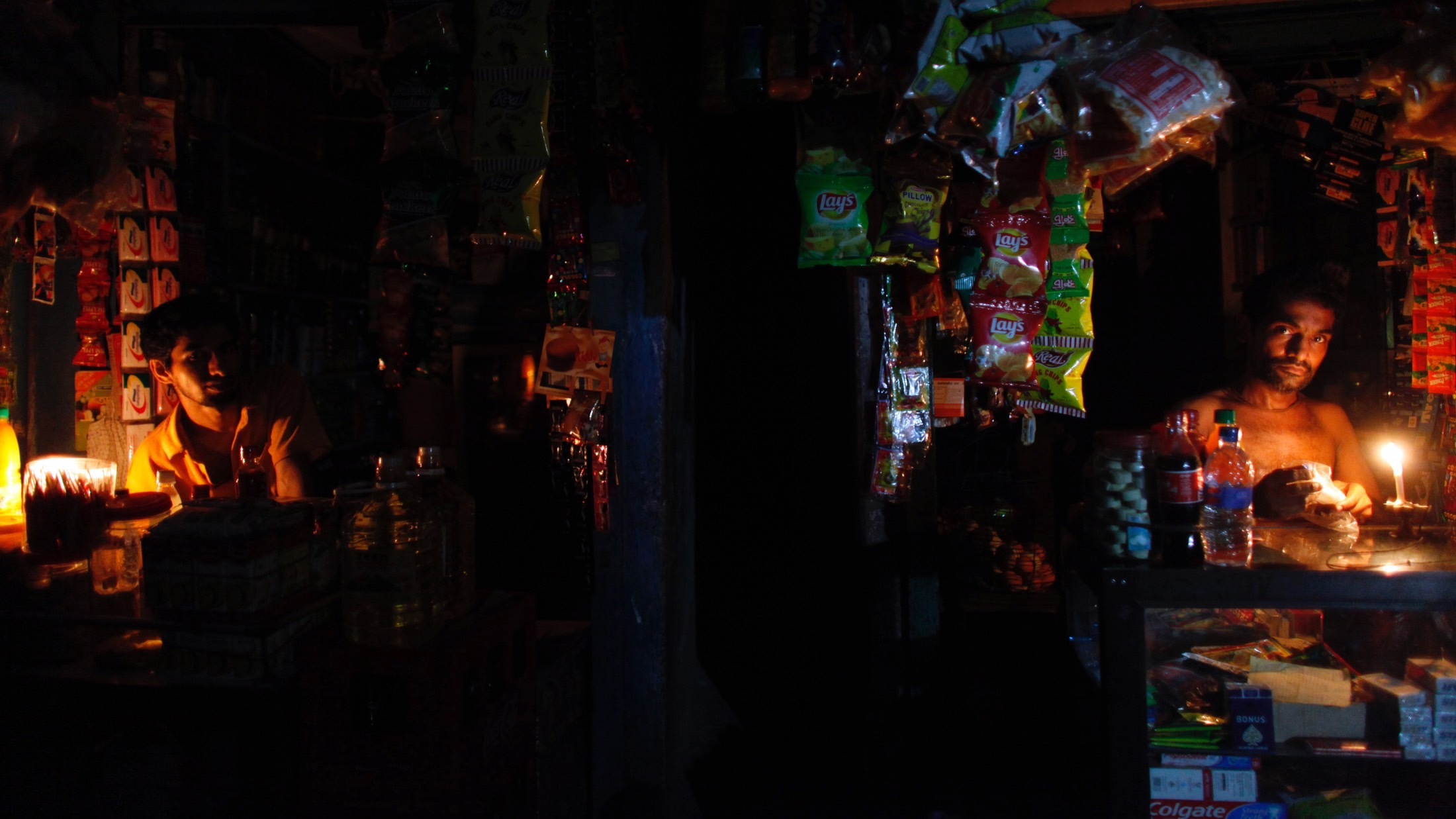 Vendors work in roadside shops during a power cut in an old part of Dhaka