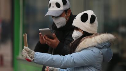 A Chinese wearing mask takes a selfie photo in a shopping street during a hazy day in Beijing city, China, 22 December 2015. Beijing issued a red alert for smog on 18 December 2015, urging schools to close and residents to stay indoors for the second time in 10 days. Restrictions began on 19 December and will last until 22 December, the city's emergency management headquarters announced on the Beijing government website. EPA/WU HONG