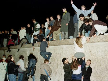 East German citizens climb the Berlin wall at the Brandenburg Gate as they celebrate the opening of the East German border in this November 10, 1989 file photo.