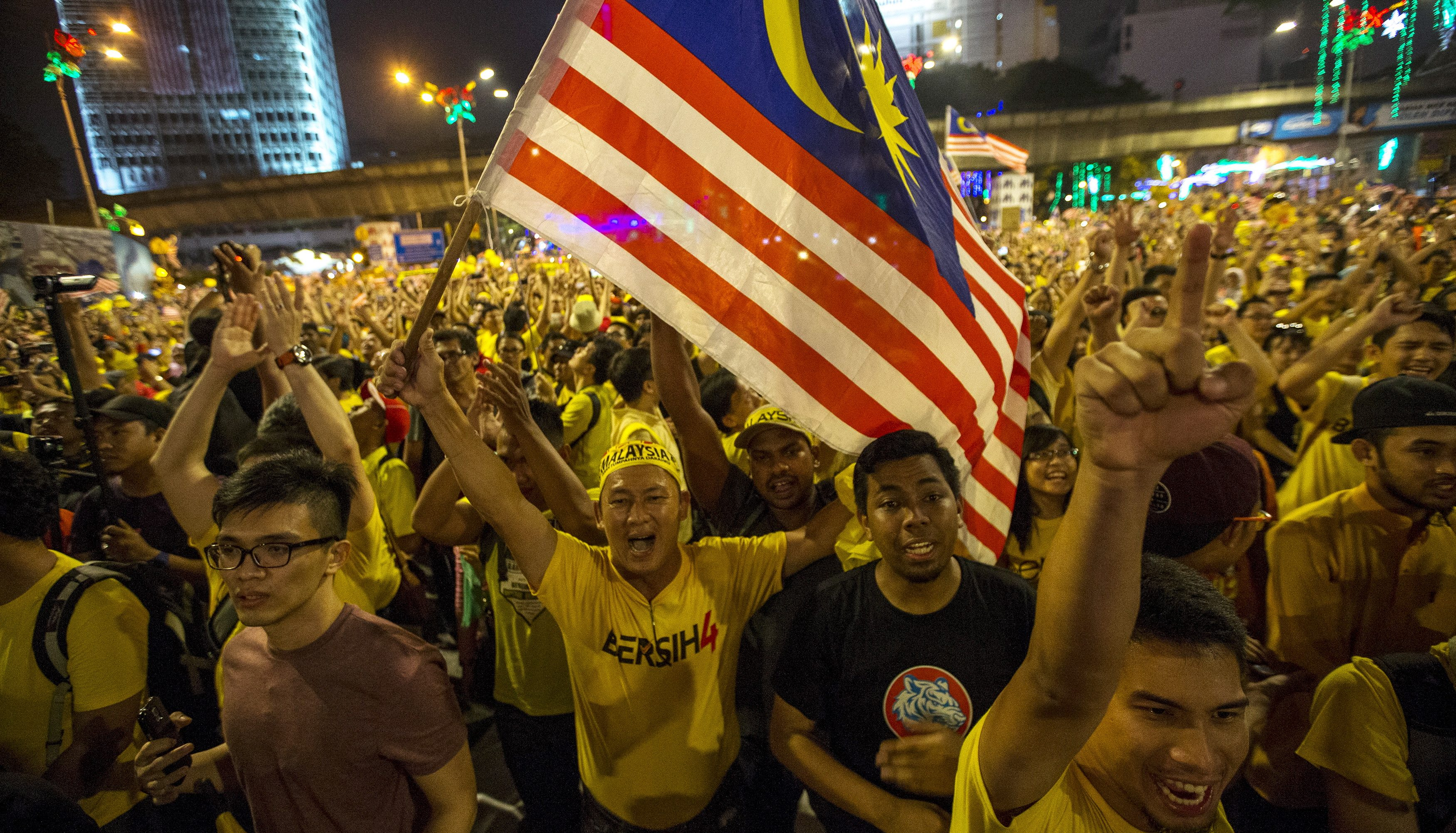 "Supporters of pro-democracy group ""Bersih"" (Clean) shout slogans during a rally near Dataran Merdeka in Malaysia's capital city of Kuala Lumpur, Malaysia,  August 30, 2015. Tens of thousands joined a peaceful protest in Kuala Lumpur on Saturday to demand the resignation of Prime Minister Najib Razak, bringing to the streets a political crisis over a multi-million-dollar payment made to an account under his name."