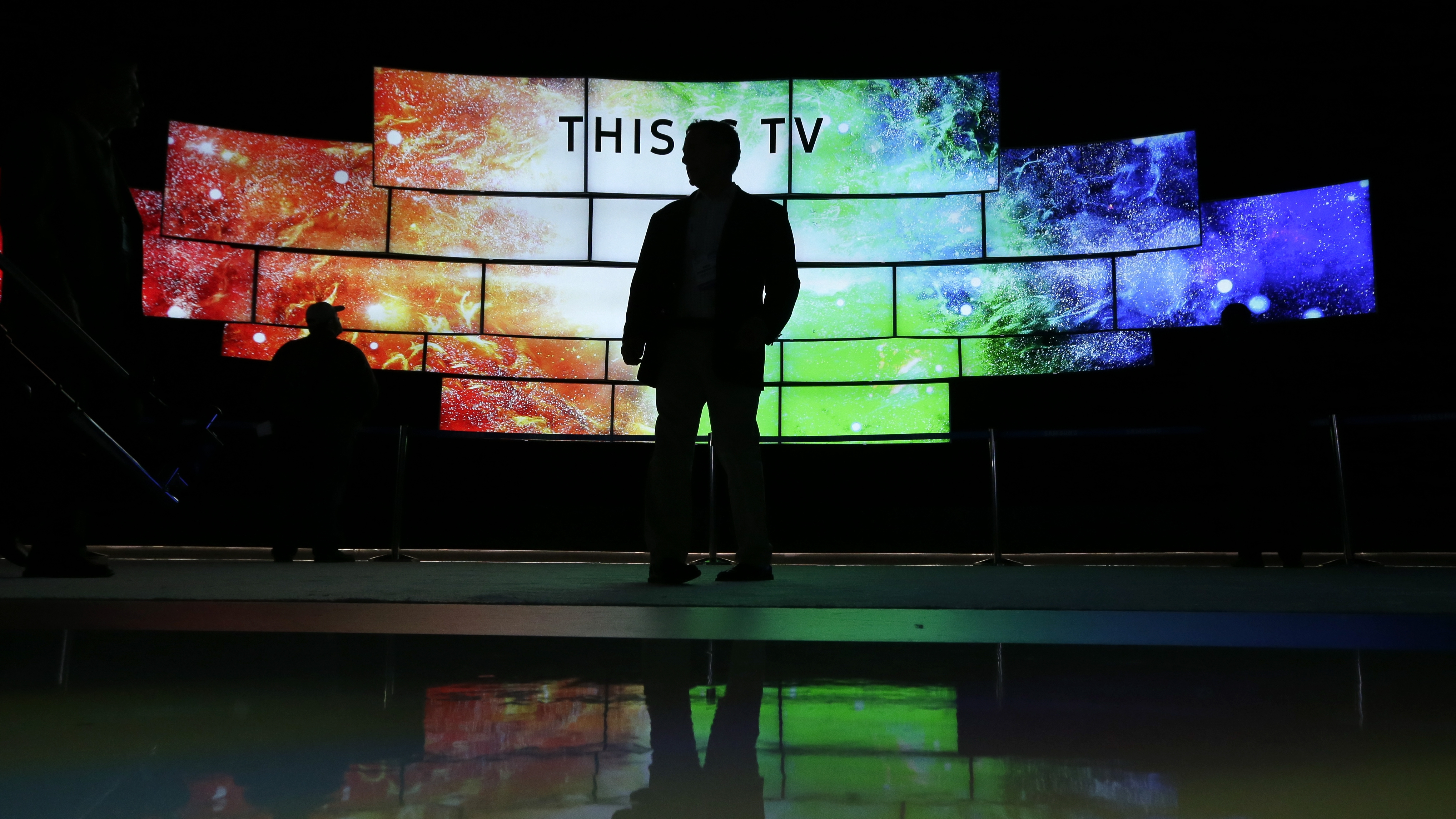 A man looks at Samsung SUHD TVs at CES International Wednesday, Jan. 6, 2016, in Las Vegas. (AP Photo/Gregory Bull)