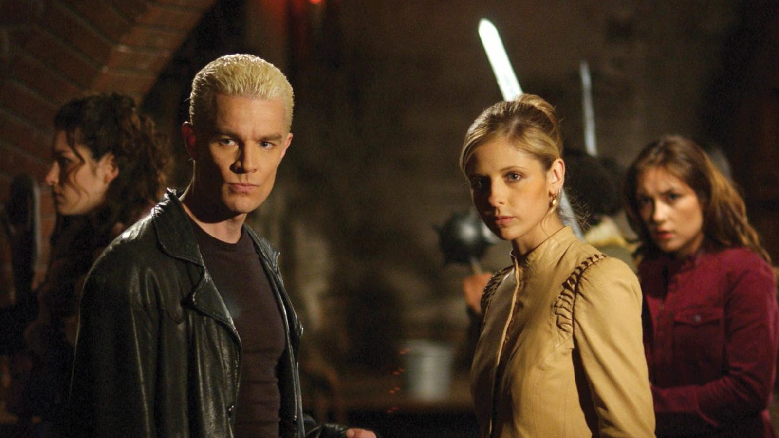 James Marsters and Sarah Michelle Gellar in Buffy the Vampire Slayer. Spike (left) and Buffy (right) appear to be stood in a dimly lit room with low brick arched ceilings. Spike has white blond hair slicked back, and a black leather jacket over a black t-shirt. Buffy, whose blonde hair is up in a neat bun, is wearing a beige shirt with detailing on the shoulders which buttons up to her neck. Both are looking off-centre, intrigued.