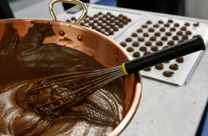A bowl of melted chocolate is pictured with chocolates