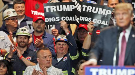 In this May 5, 2016 photo, Coal miners wave signs as Republican presidential candidate Donald Trump speaks during a rally in Charleston, W.Va. Trump's election could signal the end of many of President Barack Obama's signature environmental initiatives. Trump has said he loathes regulation and wants to use more coal and expand offshore drilling and hydraulic fracturing.