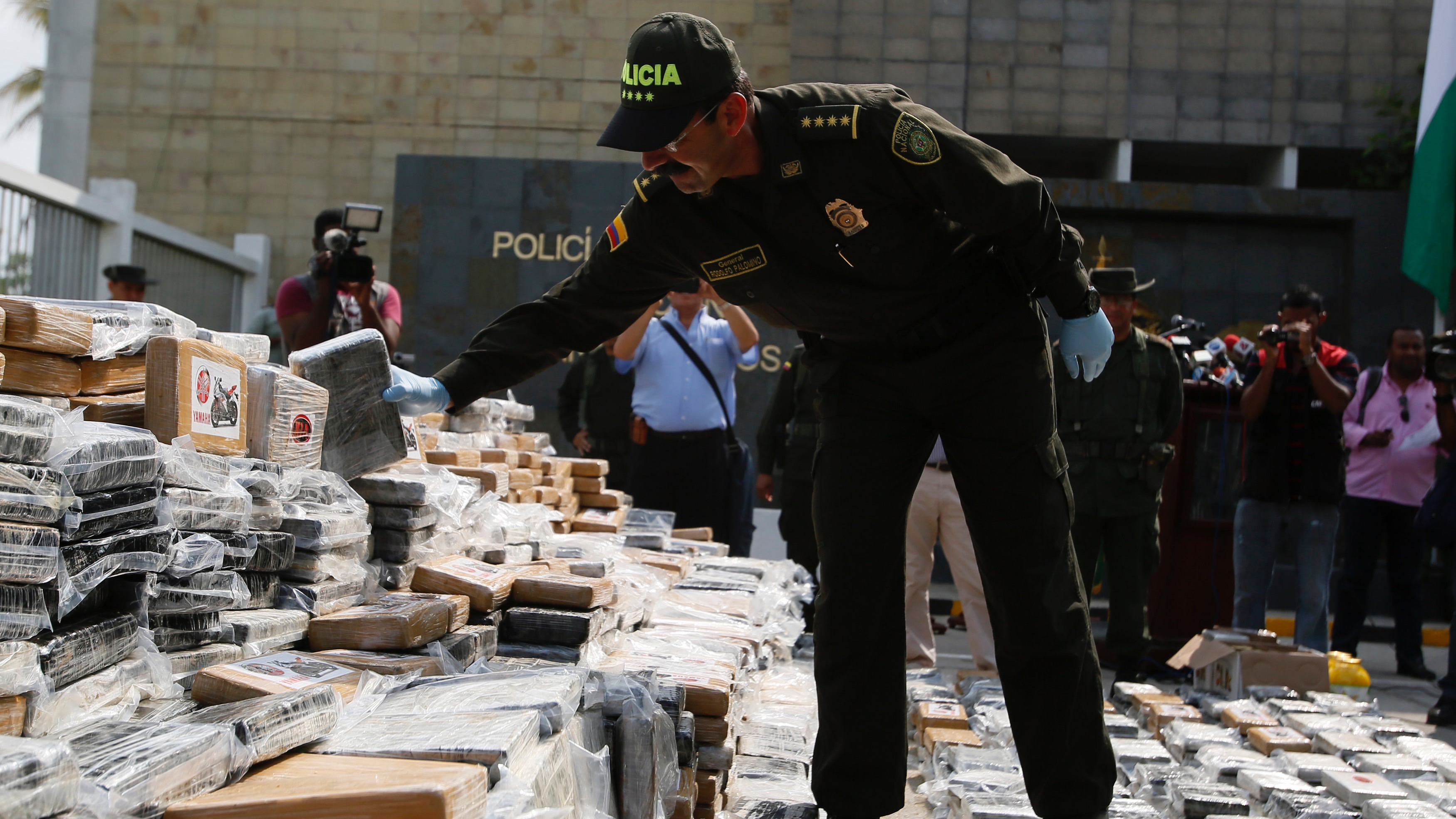 Colombia's police chief General Rodolfo Palomino examines confiscated packs of cocaine in Cartagena