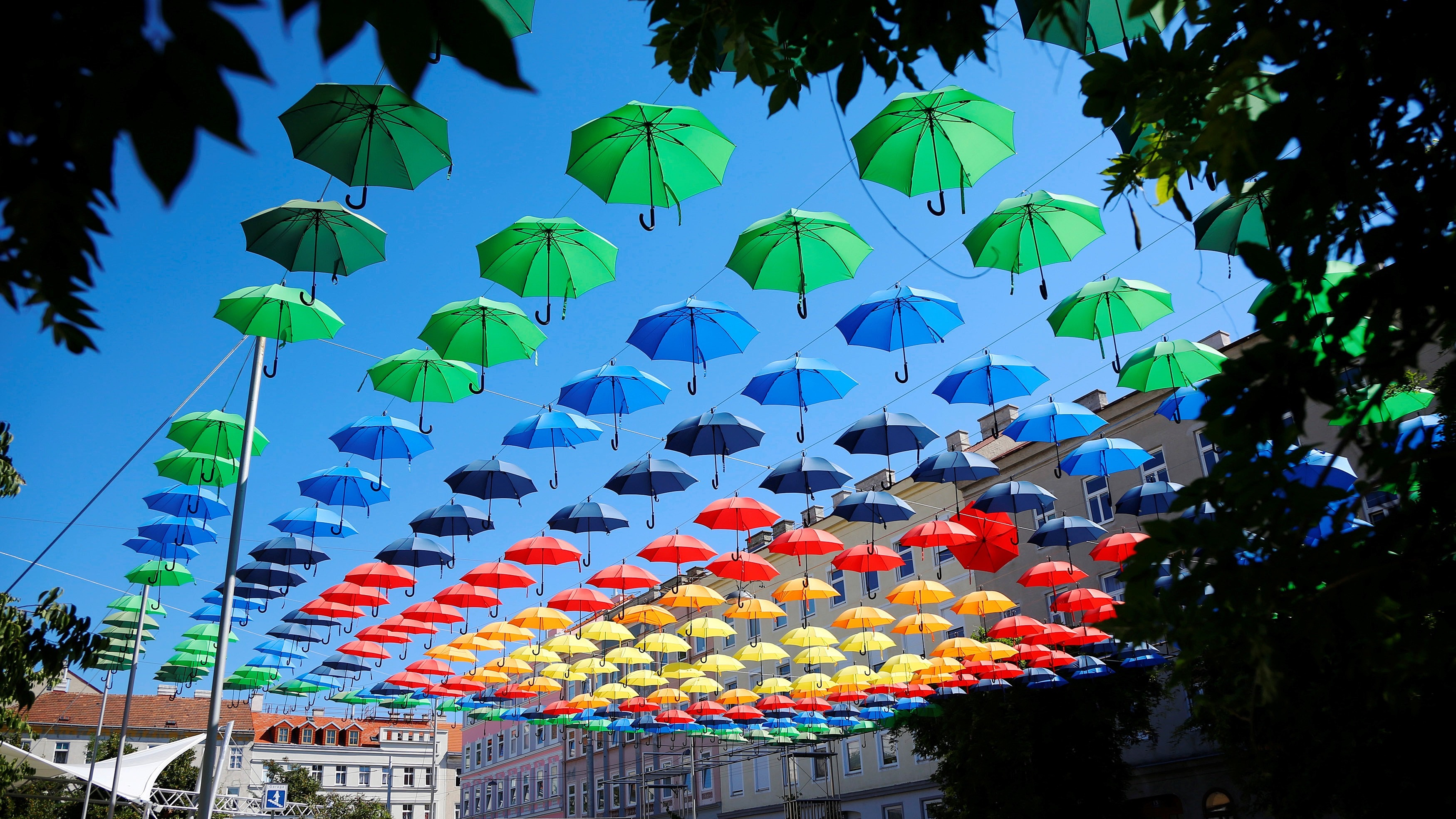 Two women walk under colourful umbrellas decorating Dorner Platz in Vienna