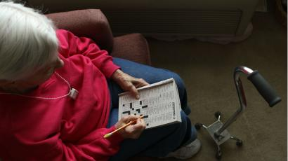 An older woman with white hair completes a crossword puzzle.