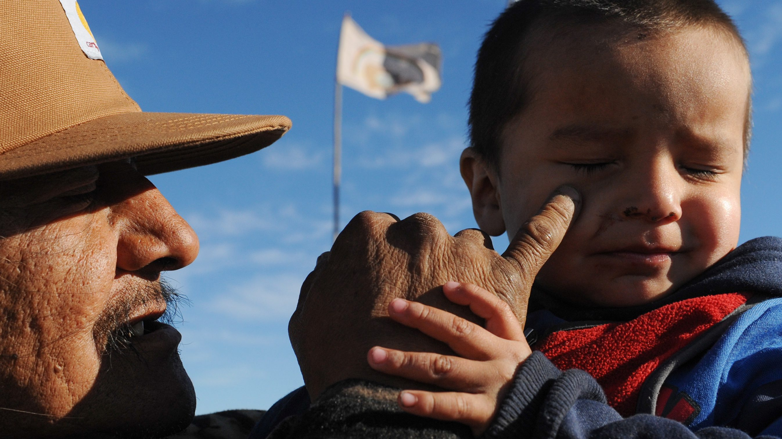 A man named Black Horse holds his grandson during a protest against the Dakota Access pipeline near the Standing Rock Indian Reservation