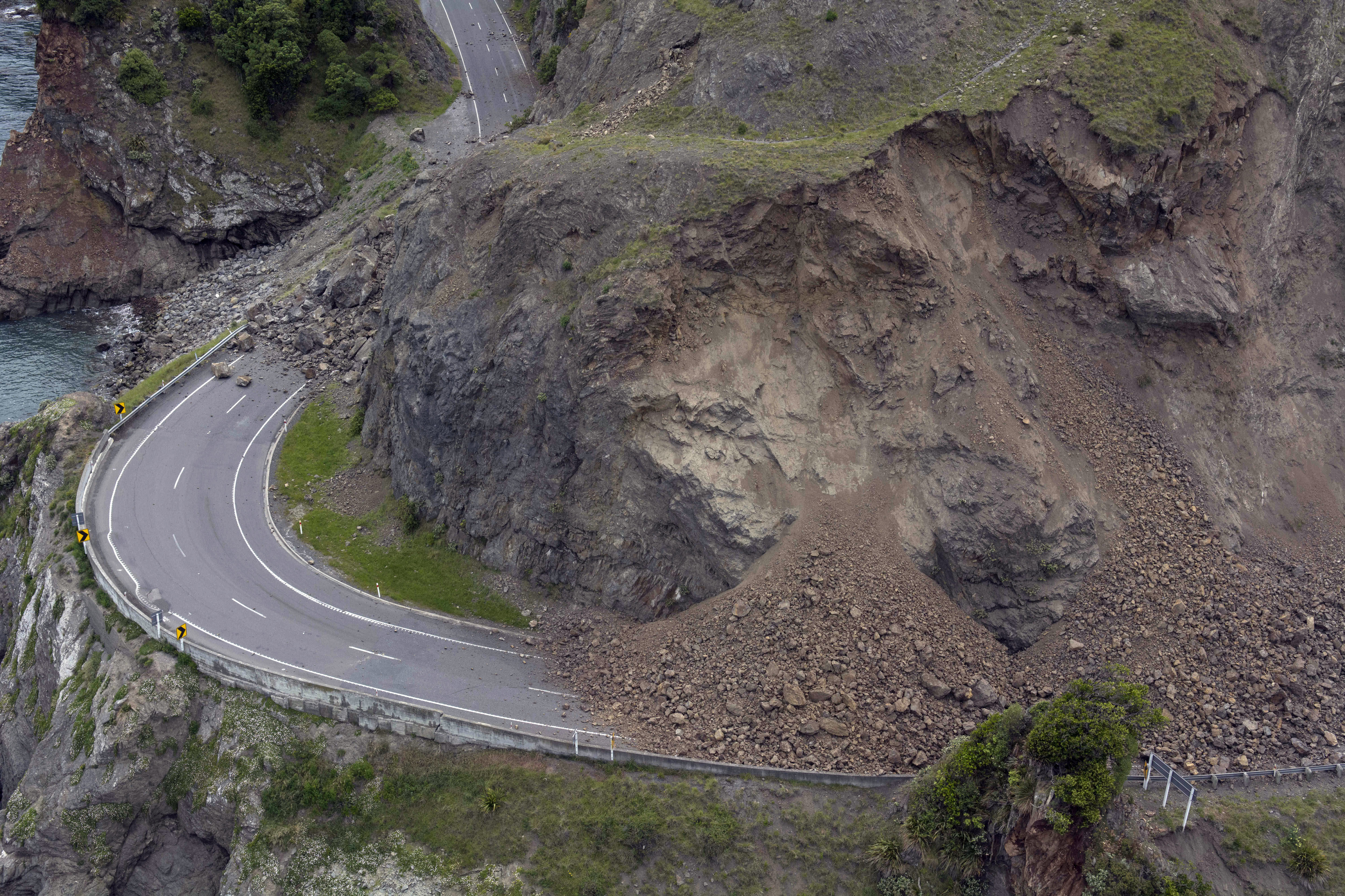 A landslide covers a section of state highway 1 near Kaikoura, New Zealand, Monday, Nov. 14, 2016, after a powerful earthquake. A powerful earthquake that rocked New Zealand on Monday triggered landslides and a small tsunami, cracked apart roads and homes, but largely spared the country the devastation it saw five years ago when a deadly earthquake struck the same region.