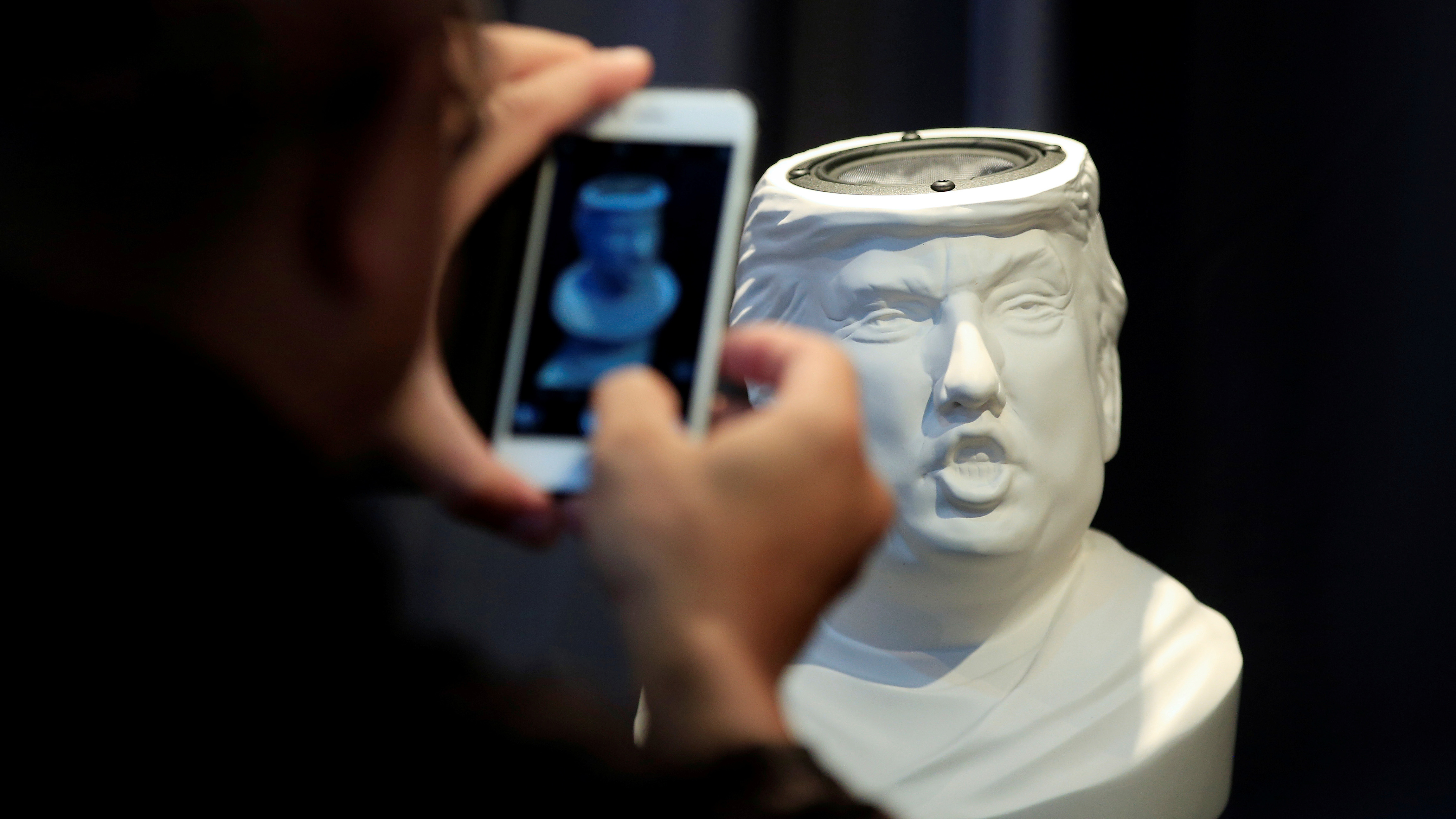 A man takes picture of a Sound Of Power speaker in the shape of a bust of Donald Trump is displayed at the CES (Consumer Electronics Show) Asia 2016 in Shanghai, China May 13, 2016. The speaker is designed by Petro Wodkins. REUTERS/Aly Song TPX IMAGES OF THE DAY - RTX2E4SG