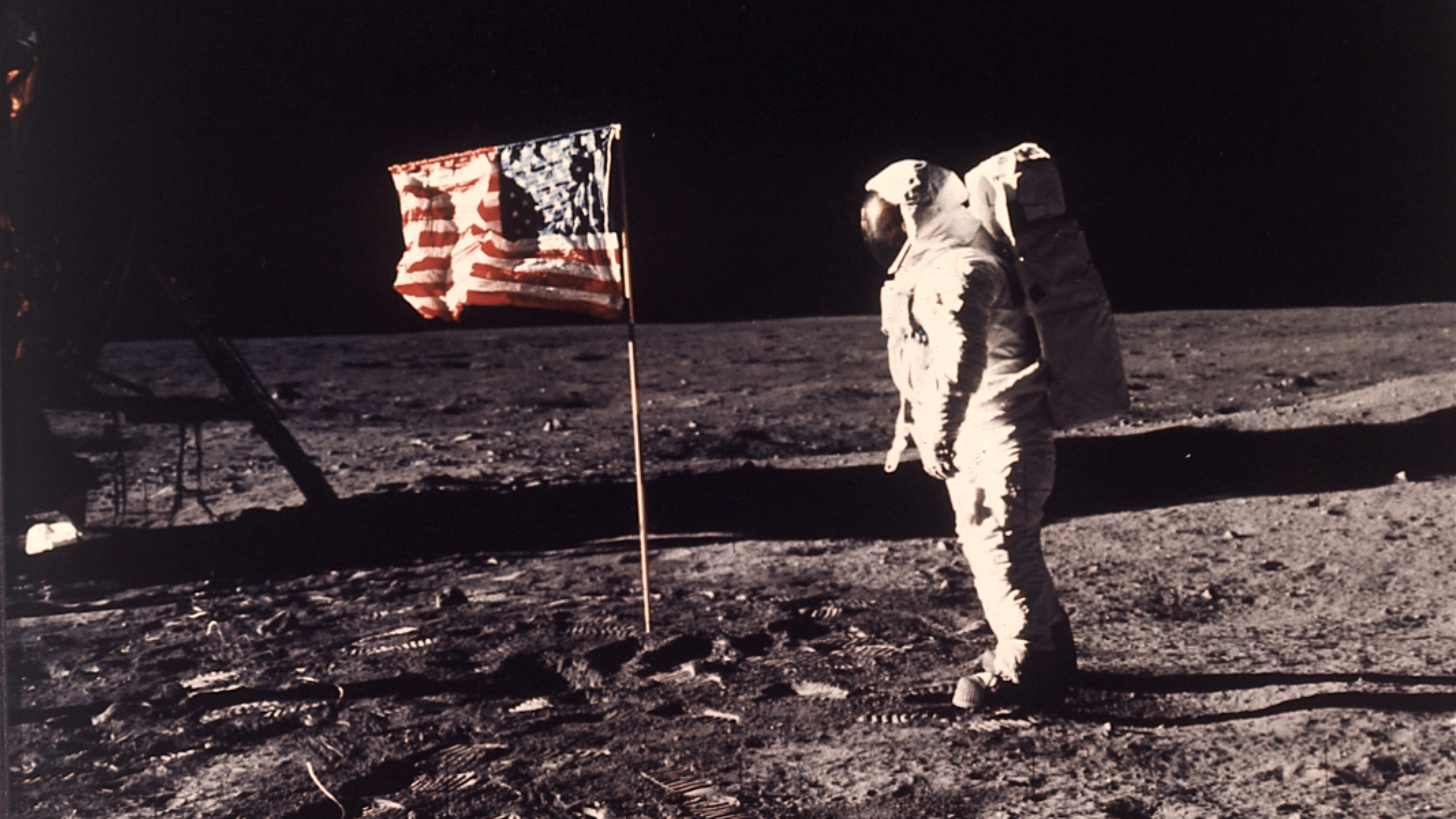 """Astronaut Edwin E. """"Buzz"""" Aldrin Jr. poses for a photograph beside the U.S. flag deployed on the moon during NASA's Apollo 11 mission on July 20, 1969."""