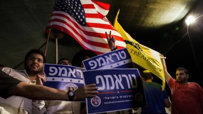 Israelis wave flags and hold signs during a rally, sponsored by Republicans Overseas Israel