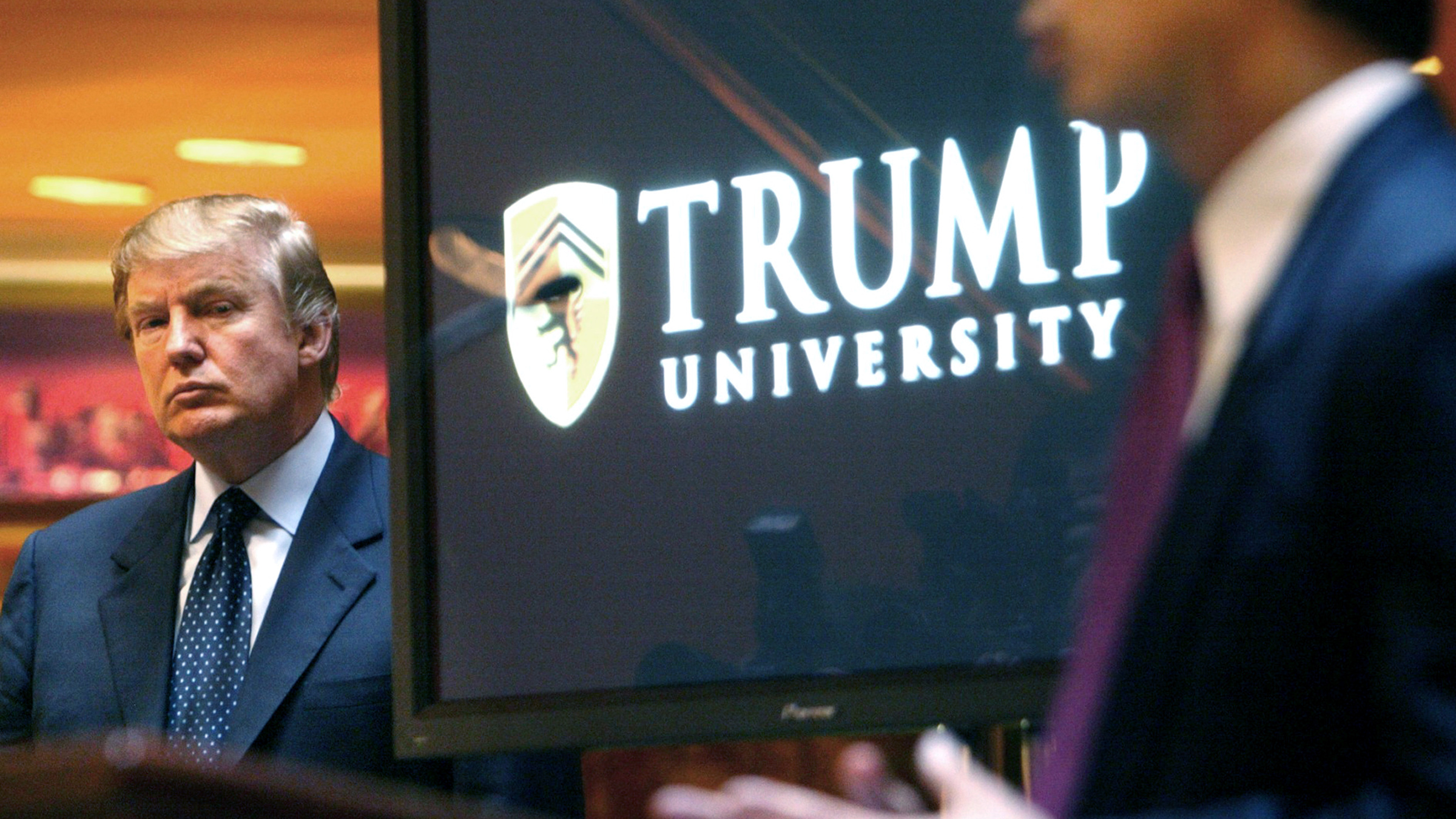 """In this May 23, 2005 file photo, real estate mogul and Reality TV star Donald Trump, left, listens as Michael Sexton introduces him at a news conference in New York where he announced the establishment of Trump University. New York Attorney General Eric Schneiderman is suing Trump for $40 million, saying that """"Trump University"""" didn't deliver on its advertised promise to make students rich, but instead steered them into expensive yet mostly useless seminars."""