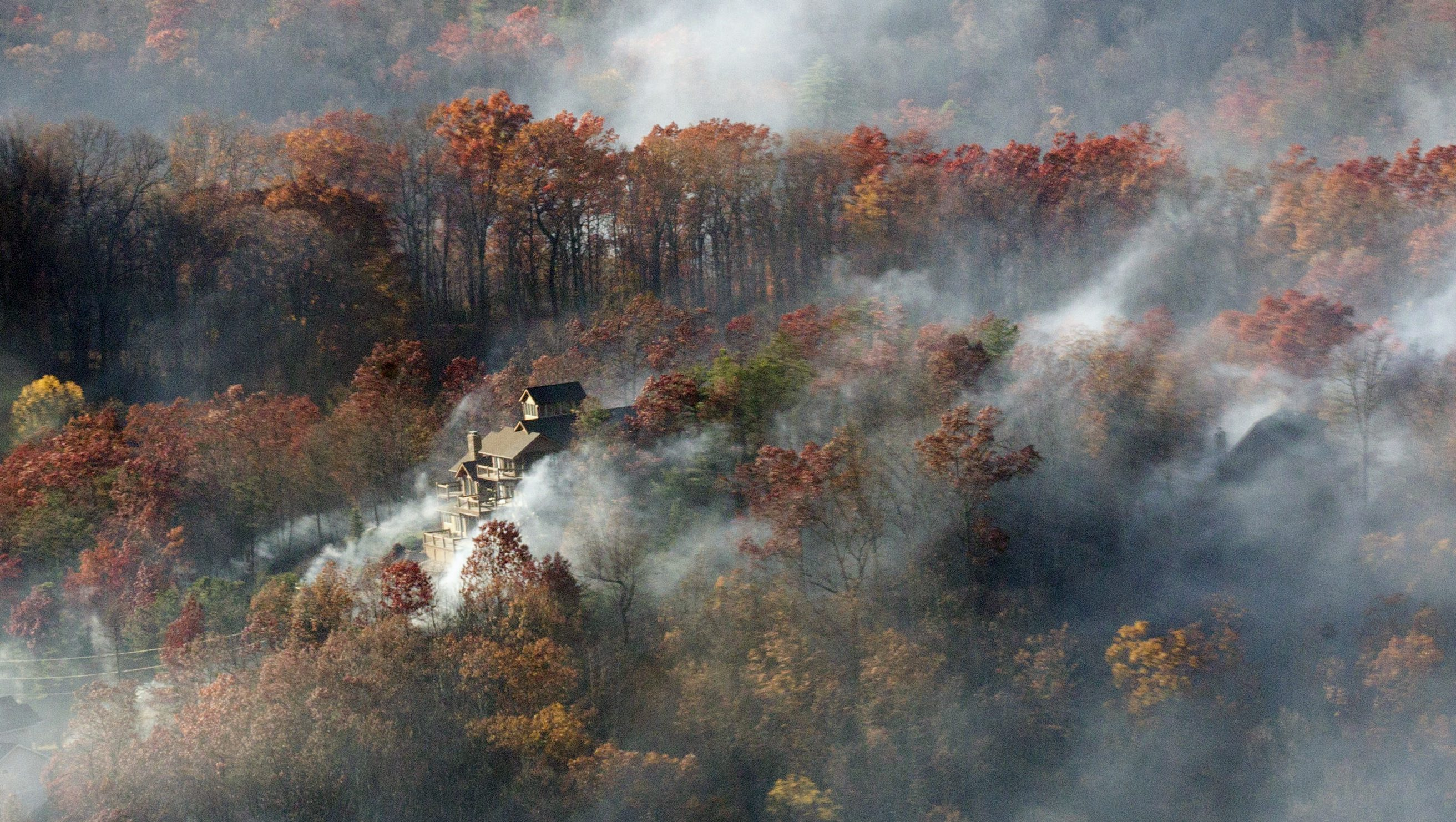 Smoke from a deadly wildfire engulfs a home near Gatlinburg, Tennessee.