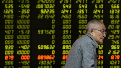An elderly stock investor walks past an electronic screen showing the stock prices at a brokerage house.