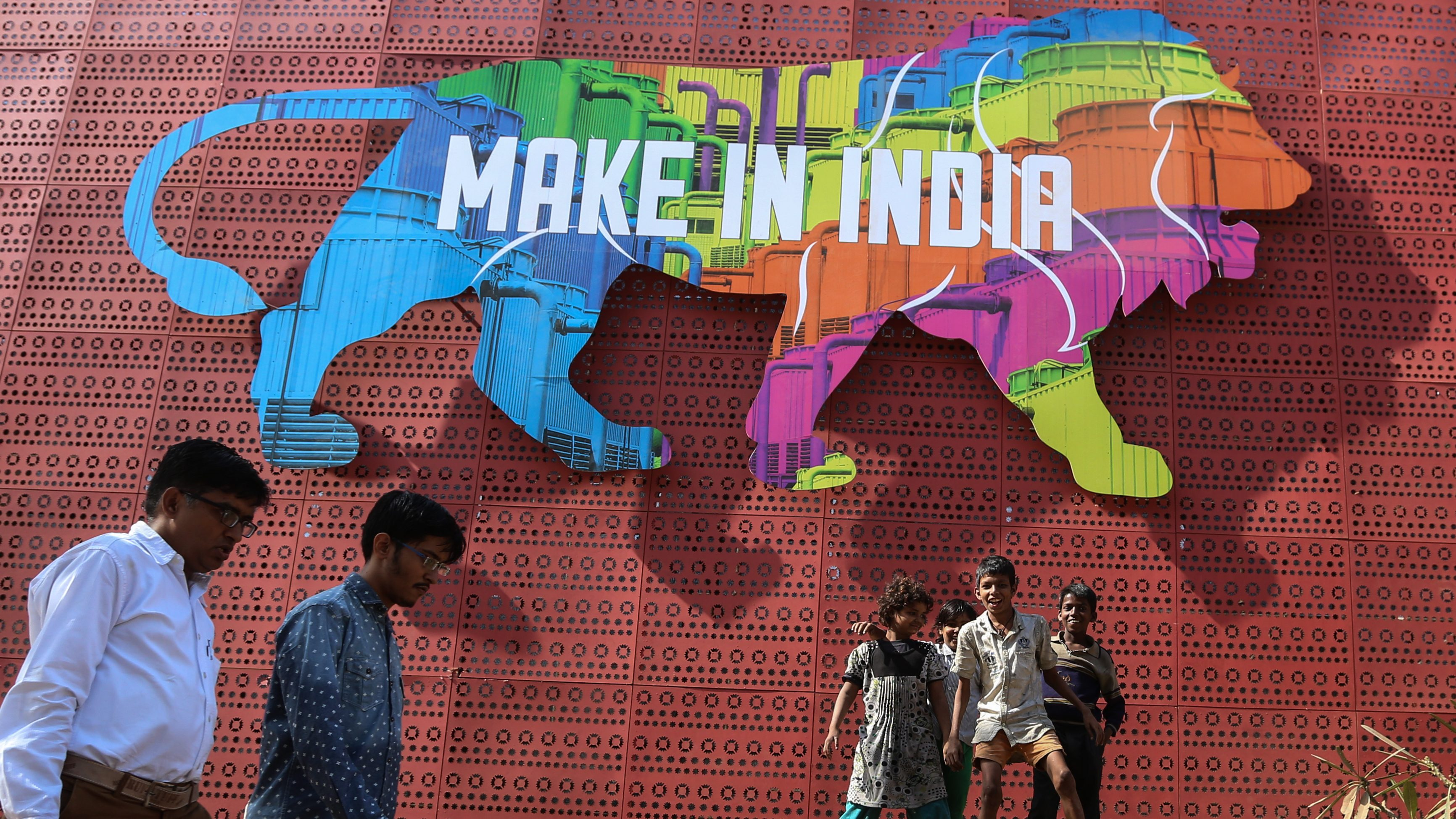 Indian people walk past as the slum childrens play around the 'Make in India' logo in Mumbai, India, 13 February 2016. The 'Make in India' campaign launched by the Indian Prime Minster Narendra Modi is aimed to attract investment and make the country a global manufacturing hub. The campaign aims to cut red bureaucracy and roll out the red carpet for investors through a string of measures that include easier investment regulations, better infrastructure and developing the workforce's skills. Mumbai is hosting 'Make in India' week from 13 to 18 February 2016.