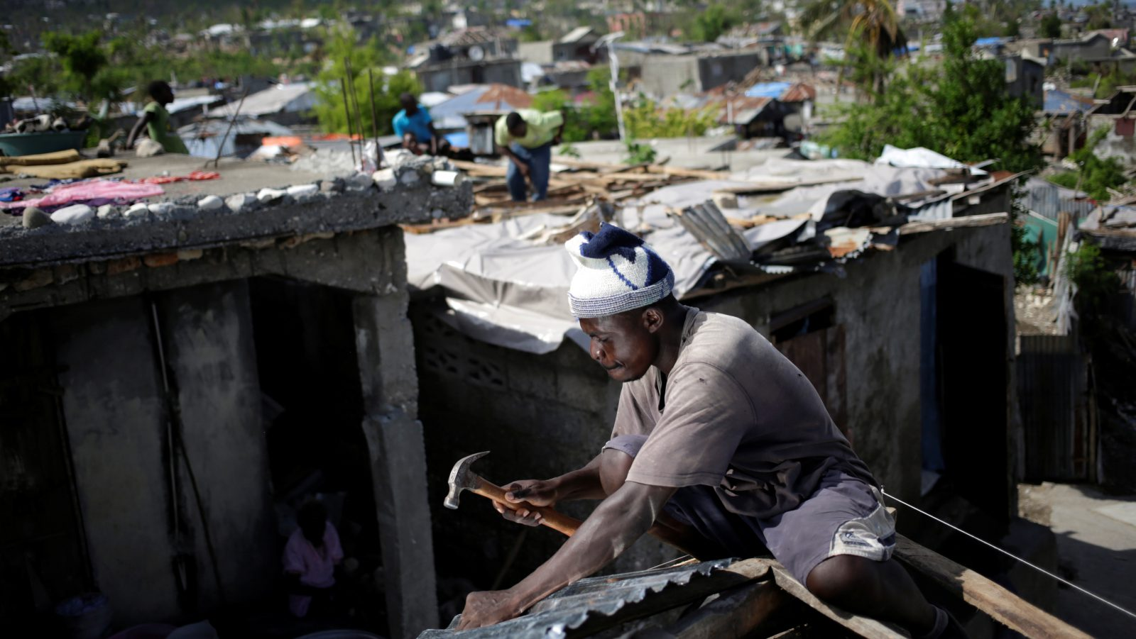 A man fixes the roof of a house affected by Hurricane Matthew in Jeremie, Haiti, October 31, 2016. REUTERS/Andres Martinez Casares - RTX2RA88