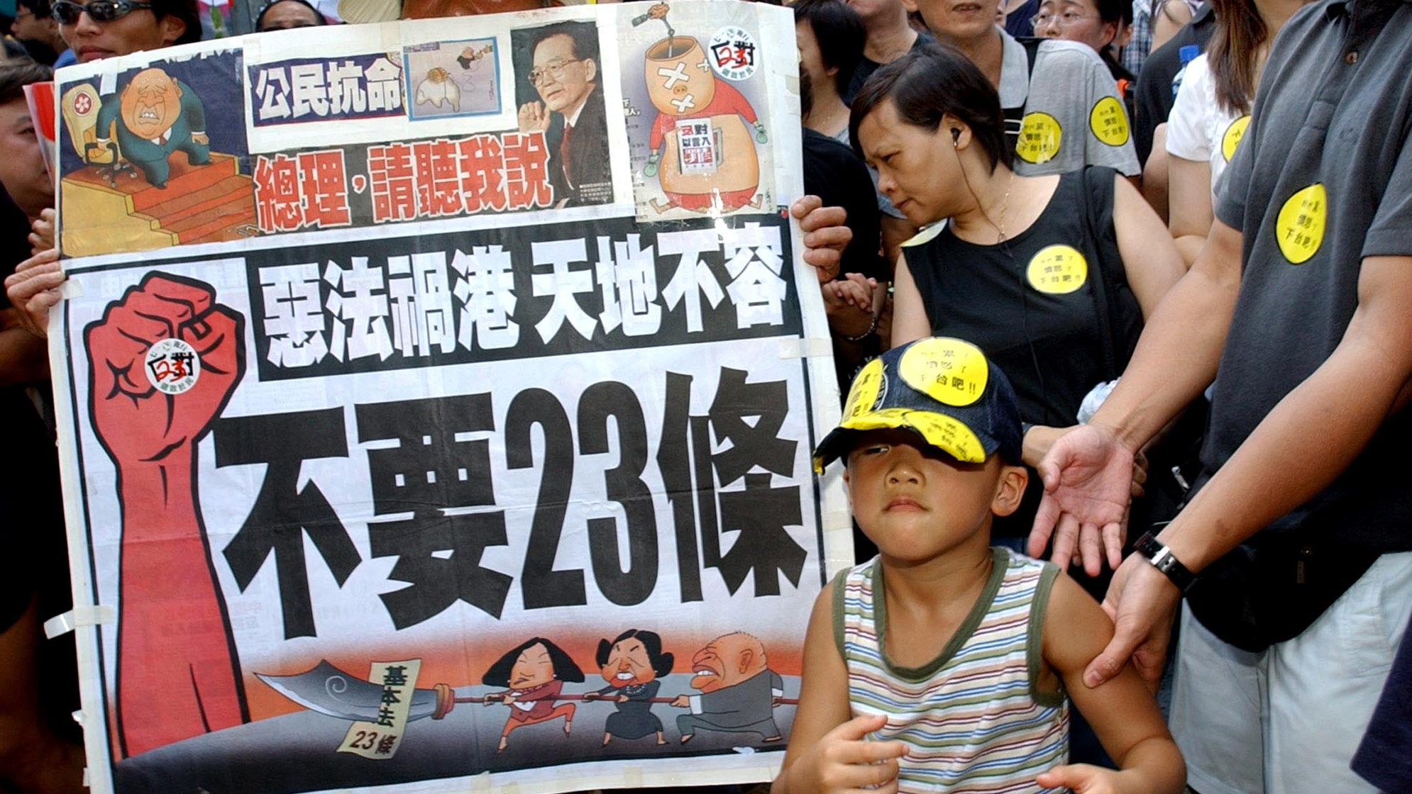 "A young protester joins protesters with a banner which reads.,""Evil law spells disaster for Hong Kong"" and ""No article 23"" as they prepare to march from a downtown park to Hong Kong's government offices Tuesday, July 1, 2003, to protest a planned anti-subversion law known also as Article 23, that has stirred one of the biggest controversies since Britain returned Hong Kong to China six years ago. Tens of thousands of people turned out to protest on the anniversary of Hong Kong's handover. (AP Photo/Anat Givon)"