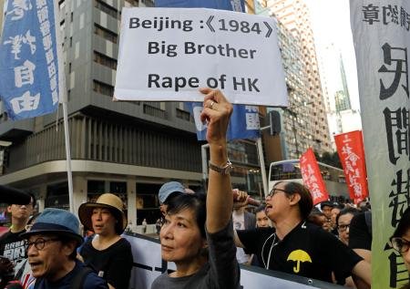A protester raises a placard as thousands of people march through a downtown street in Hong Kong, Sunday, Nov. 6, 2016, to protest Beijing's involvement in the recent legislature spat involving two newly elected separatist lawmakers. China's top legislative panel has said Beijing must intervene in a Hong Kong political dispute to deter advocates of independence for the city, calling such acts a threat to national security. (AP Photo/Vincent Yu)