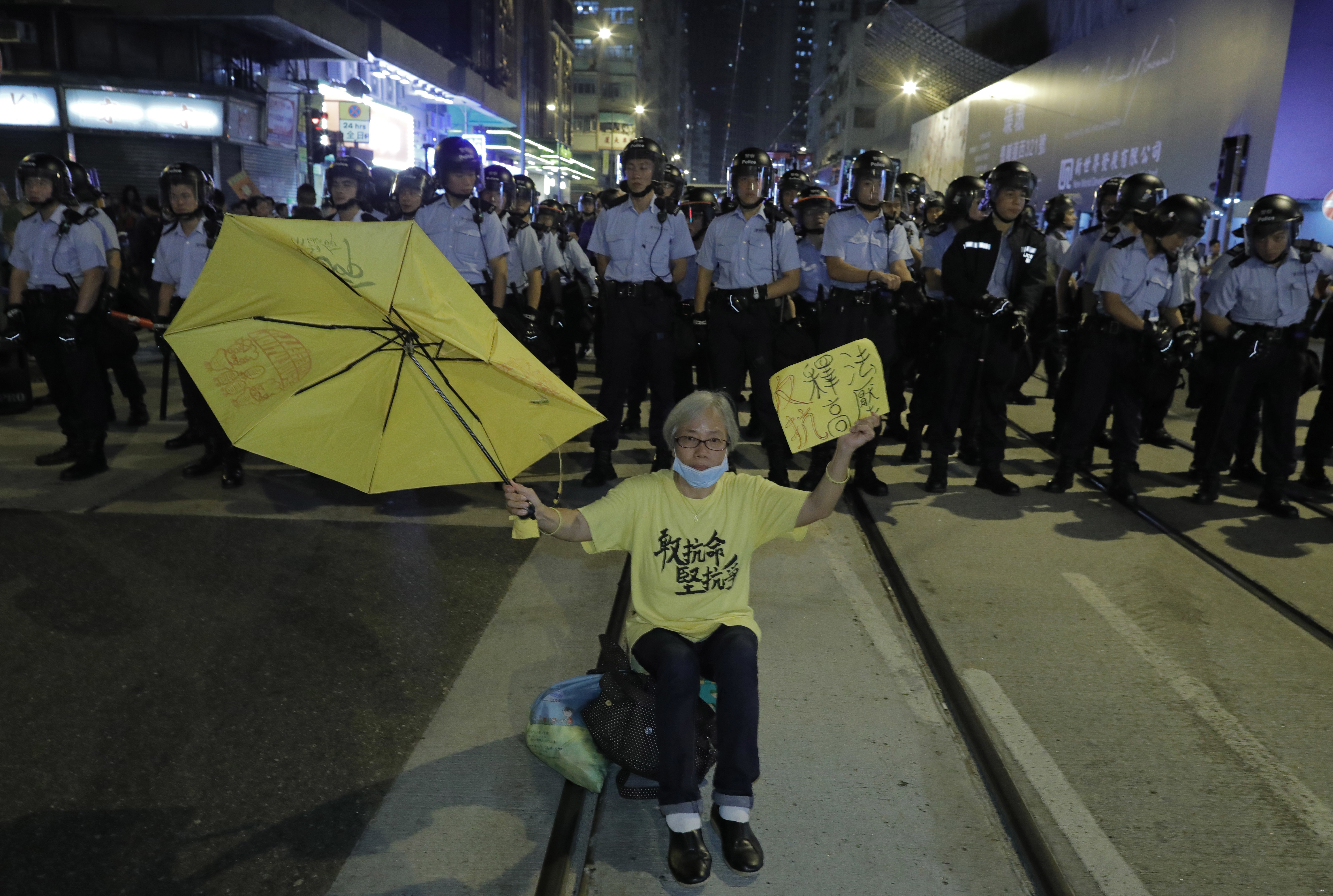 A protester raises an umbrella sitting in front of a line of police officers outside the Chinese central government's liaison office in Hong Kong, Sunday, Nov. 6, 2016. Thousands of protesters marched in Hong Kong on Sunday, demanding that China's central government stay out of a political dispute in the southern Chinese city after Beijing indicated that it would intervene to deter pro-independence advocates. (AP Photo/Vincent Yu)