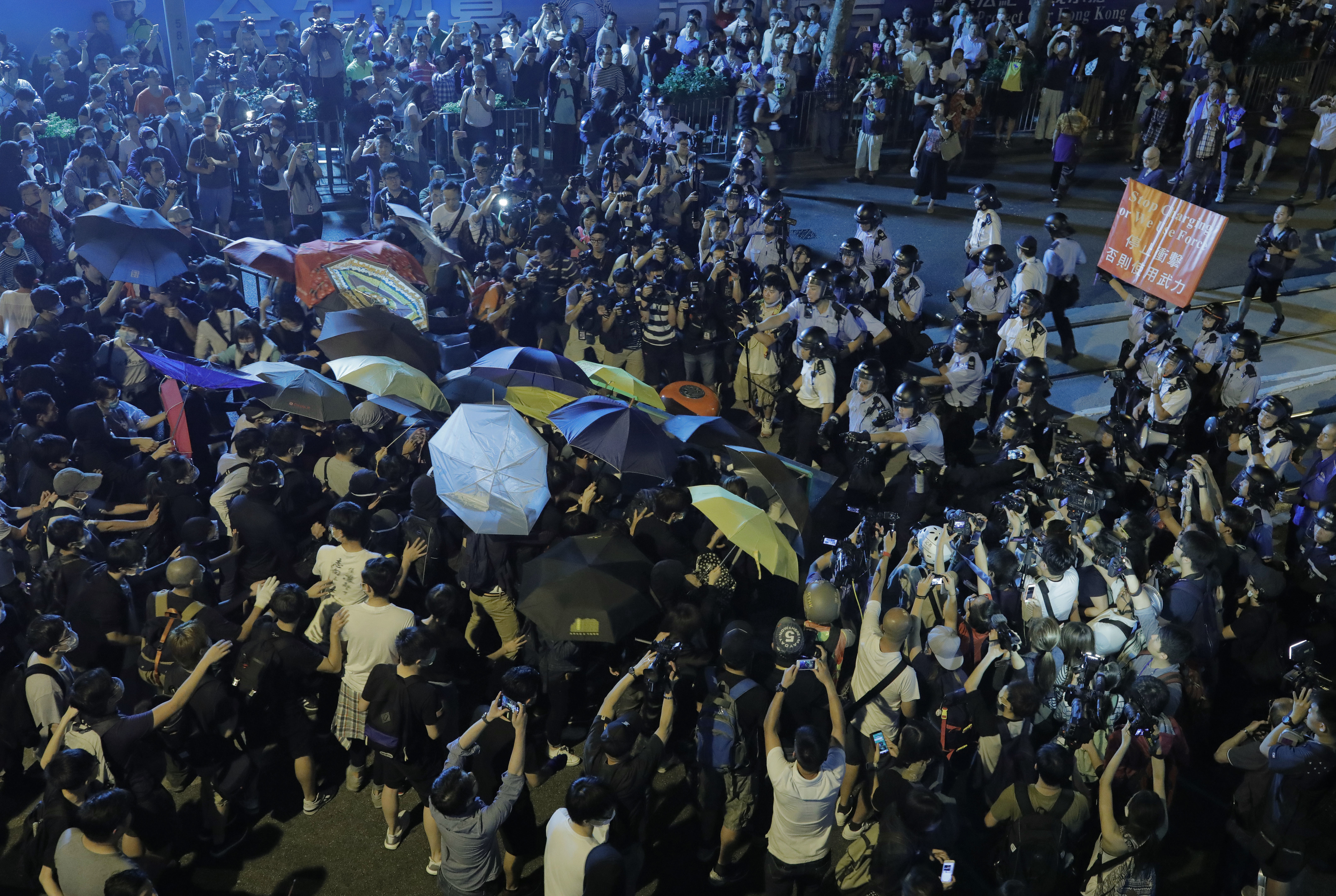 Protesters use umbrellas to block the pepper spray from office officers outside the Chinese central government's liaison office in Hong Kong, Sunday, Nov. 6, 2016. Thousands of protesters marched in Hong Kong on Sunday, demanding that China's central government stay out of a political dispute in the southern Chinese city after Beijing indicated that it would intervene to deter pro-independence advocates. (AP Photo/Vincent Yu)