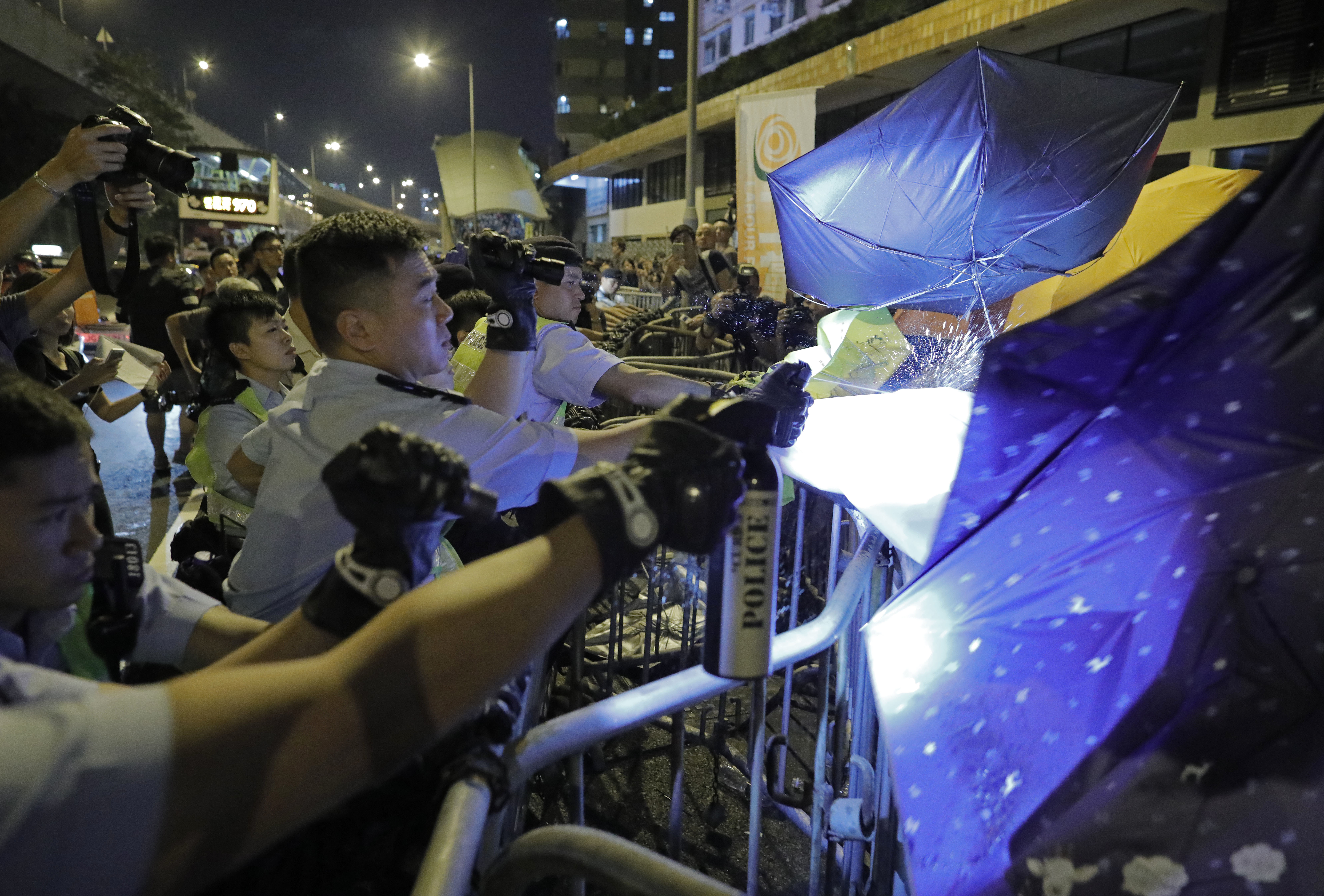 Protesters use umbrellas to block the pepper spray from police officers after clashing outside the Chinese central government's liaison office as thousands of people march in a Hong Kong down town street, Sunday, Nov. 6, 2016, to protest China's top legislative panel has said Beijing must intervene in a Hong Kong political dispute to deter advocates of independence for the city, calling such acts a threat to national security. (AP Photo/Vincent Yu)