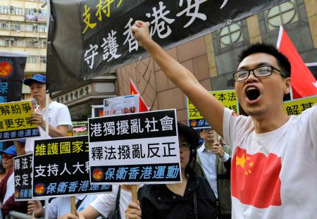 A pro-China supporter shouts slogans as thousands of protesters march through a downtown street in Hong Kong, Sunday, Nov. 6, 2016, to protest Beijing's involvement in the recent legislature spat involving two newly elected separatist lawmakers. China's top legislative panel has said Beijing must intervene in a Hong Kong political dispute to deter advocates of independence for the city, calling such acts a threat to national security. (AP Photo/Vincent Yu)
