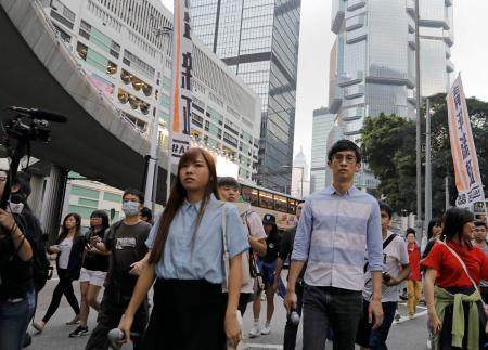 Newly elected Hong Kong lawmakers Yau Wai-ching, left, and Sixtus Leung, march along with thousands of people through downtown Hong Kong, Sunday, Nov. 6, 2016, to protest Beijing's involvement in the recent legislature spat involving the lawmakers. China's top legislative panel has said Beijing must intervene in a Hong Kong political dispute to deter advocates of independence for the city, calling such acts a threat to national security. (AP Photo/Vincent Yu)