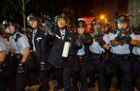 Police armed with pepper spray prepare to confront protestors gathered outside the Chinese government's headquarters in Hong Kong, China, 06 November 2016. Thousands of protestors marched through the streets of Hong Kong to demonstrate against the Chinese government's controversial decision to decide the fate of two Hong Kong lawmakers who refused to pledge allegiance to the Hong Kong constitution and swore featly to the Hong Kong nation instead. EPA/ALEX HOFFORD