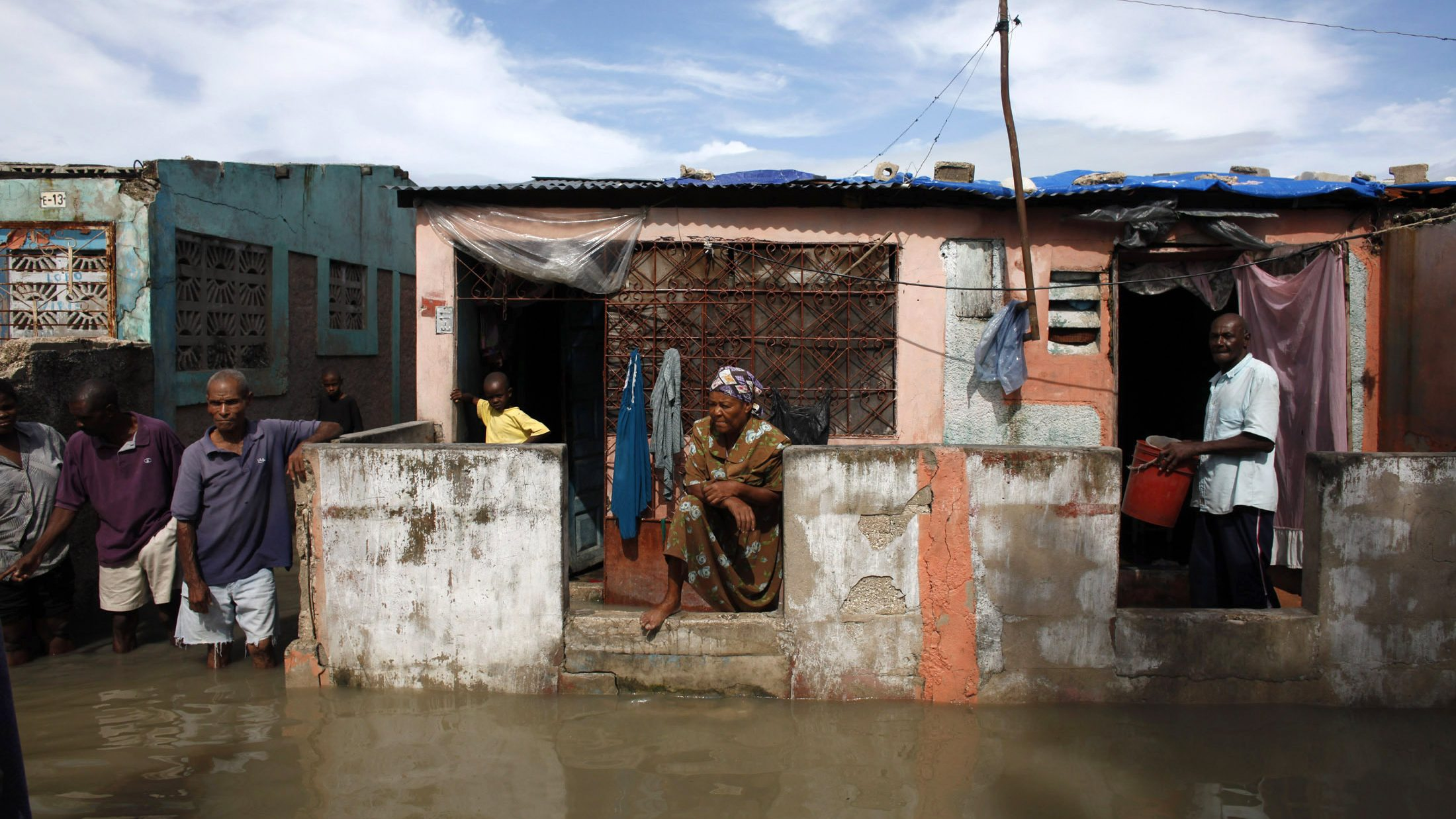 Haitians wait for help after a drain flooded their neighborhood of Cite-Soleil in Port-au-Prince November 6, 2010. Hurricane Tomas soaked Haiti's crowded earthquake survivors' camps and swamped coastal towns on Friday, triggering flooding and mudslides that killed at least seven people.