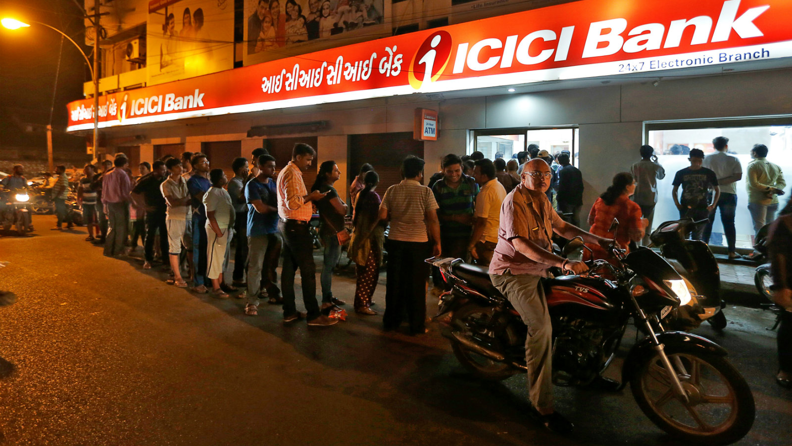 People wait to deposit and withdraw their money outside an ICICI Bank ATM in Rajkot, India, November 8, 2016.