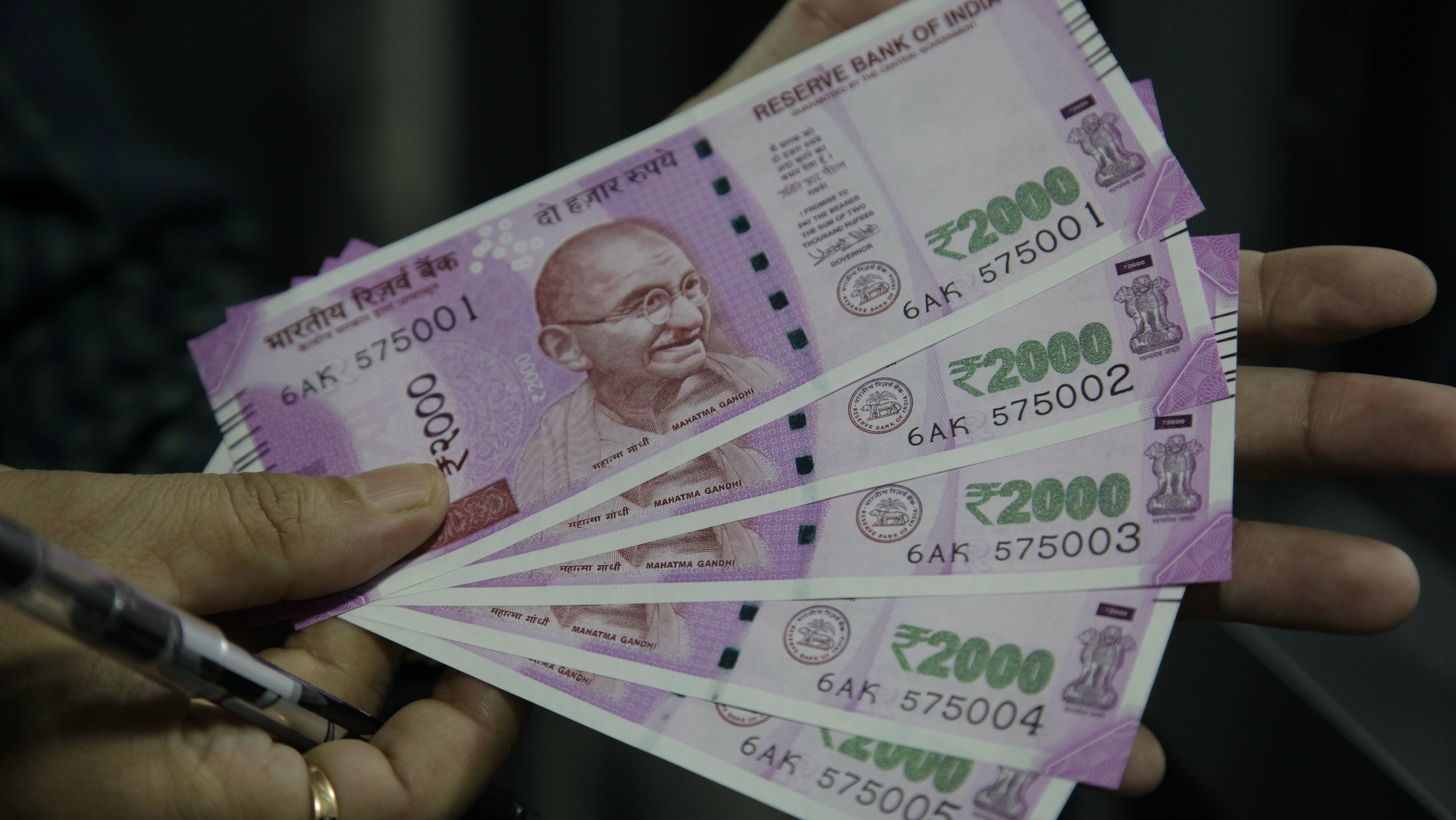 An Indian shows new rupees 2000 currency he received after exchanging discontinued currency notes in Jammu, India, Sunday, Nov. 13, 2016. Chaotic scenes played out across India over the weekend, with long lines growing even longer and scuffles breaking out, as millions of anxious people tried to change old currency notes that became worthless days earlier when the government demonetized high-value bills.