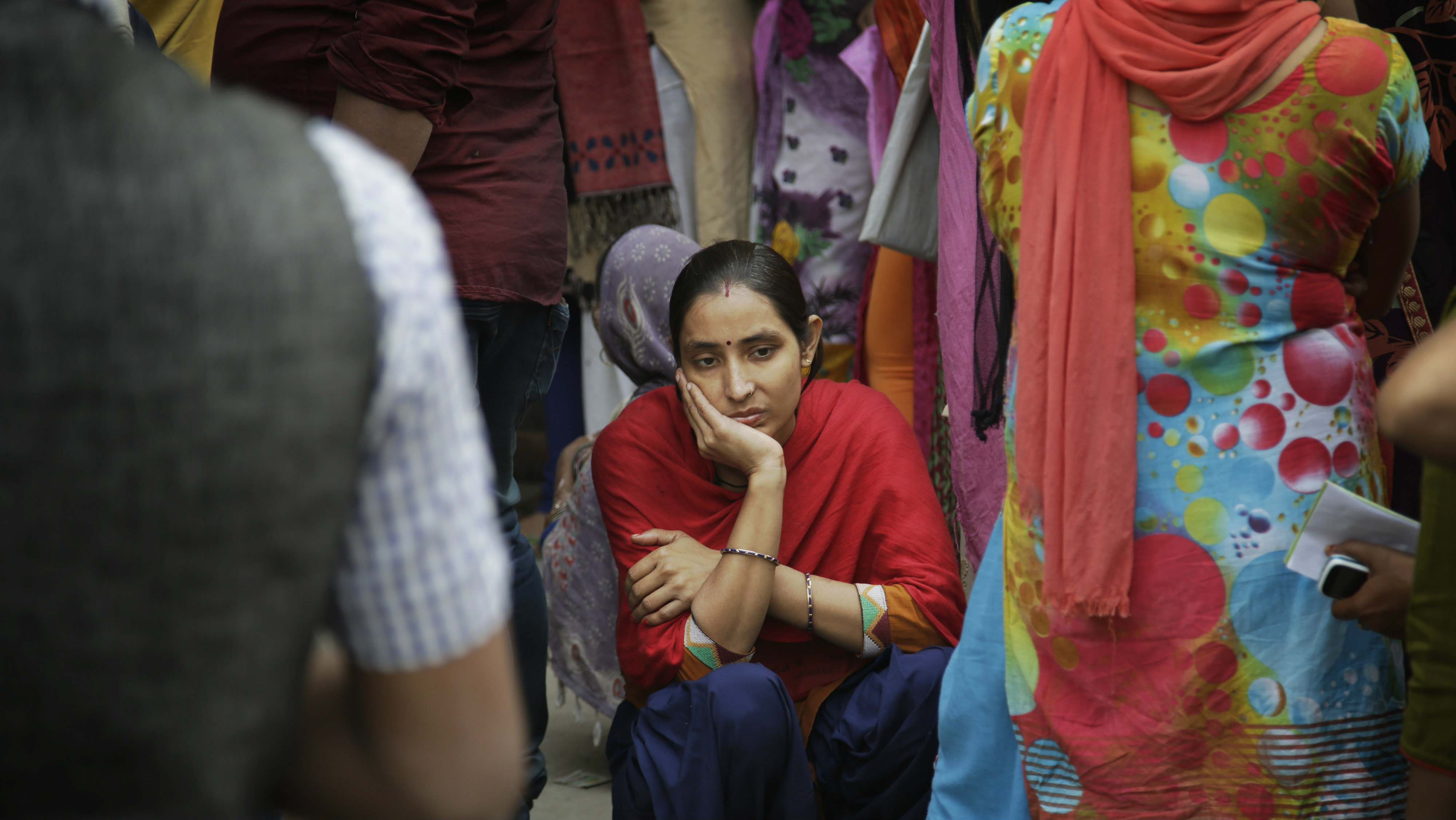 An Indian woman squats on the ground while waiting in a queue to deposit and exchange discontinued currency notes outside a bank on the outskirts of New Delhi, India, Tuesday, Nov. 15, 2016. India's government said Tuesday that it will mark the fingers of people swapping scrapped currency notes at banks with indelible ink as authorities struggle to deal with the corruption and bedlam spawned by the demonetizing of the country's highest denomination currency.