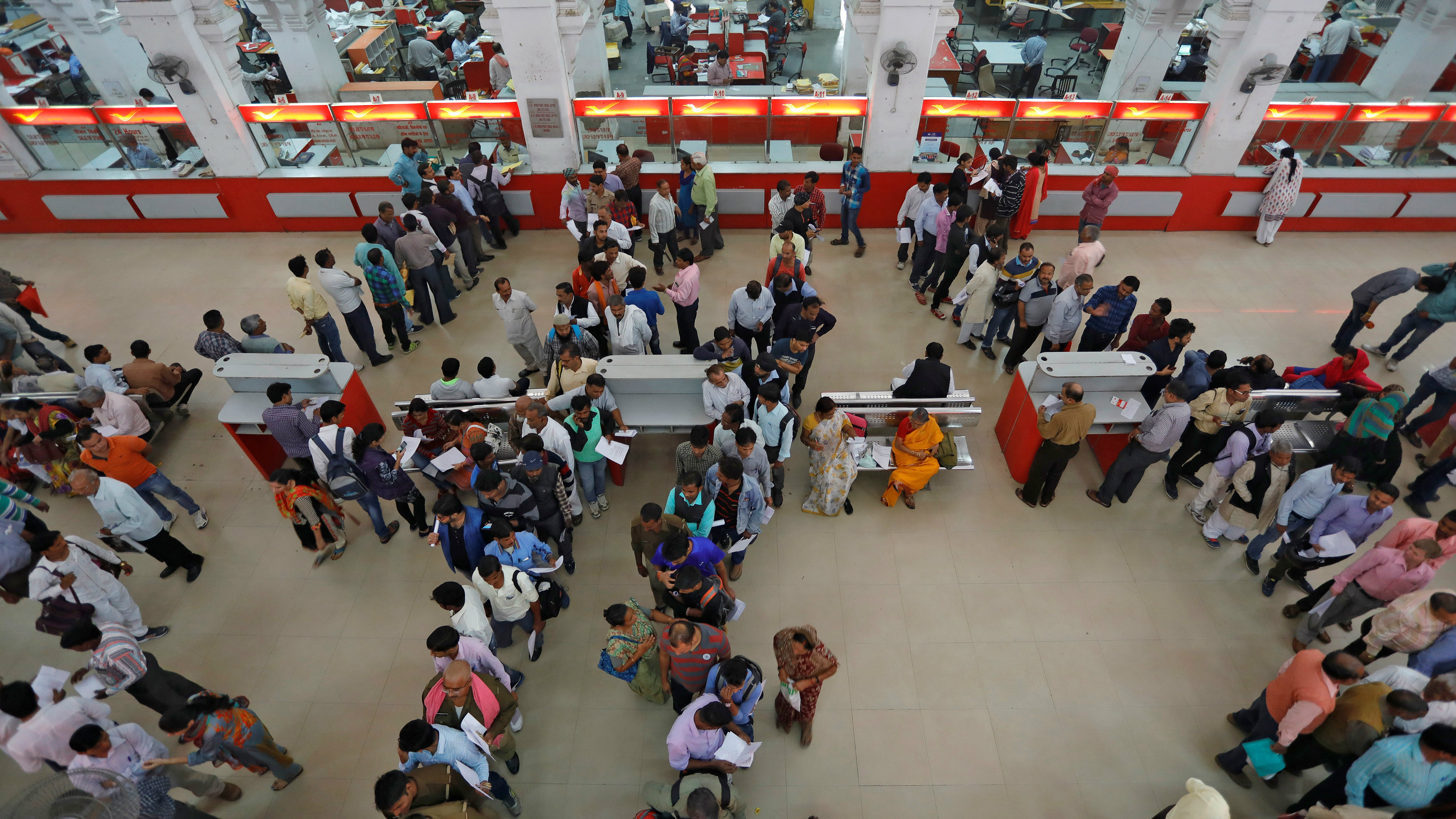 People wait in lines to deposit and withdraw money inside a post office in Lucknow, India, November 10, 2016.