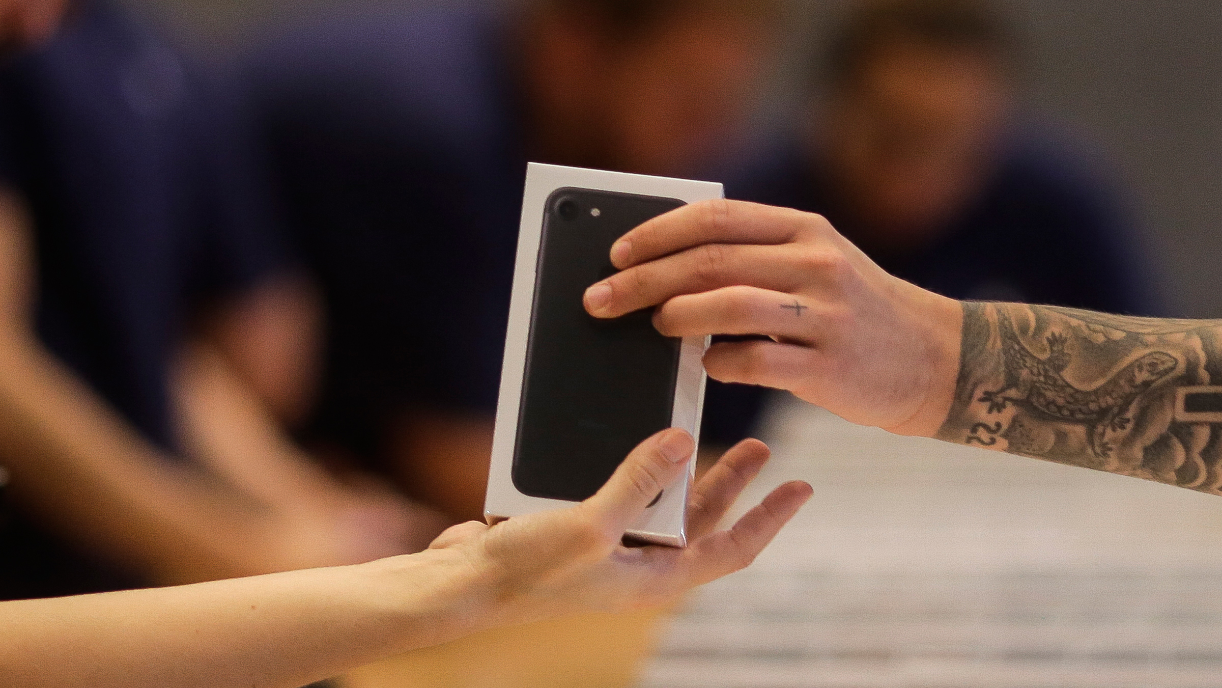 Apple shop staff hand out the new iPhone 7 to customers at the Apple store in Berlin, Friday, Sept. 16, 2016. Apple's newest mobile devices, the iPhone 7 and 7 Plus went on sale in the country on Friday. (AP Photo/Markus Schreiber)