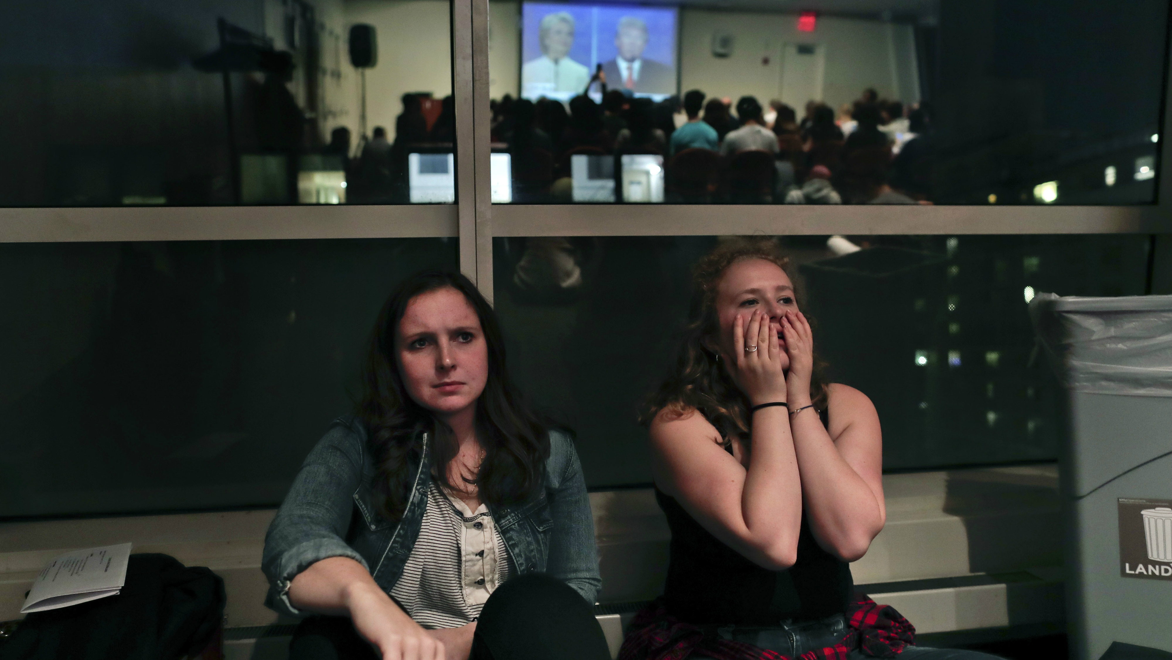 NYU students react while watching the presidential debate between Democratic candidate Hillary Clinton and Republican candidate Donald Trump during a debate watch gathering, Wednesday, Oct. 19, 2016, in New York. (AP Photo/Julie Jacobson