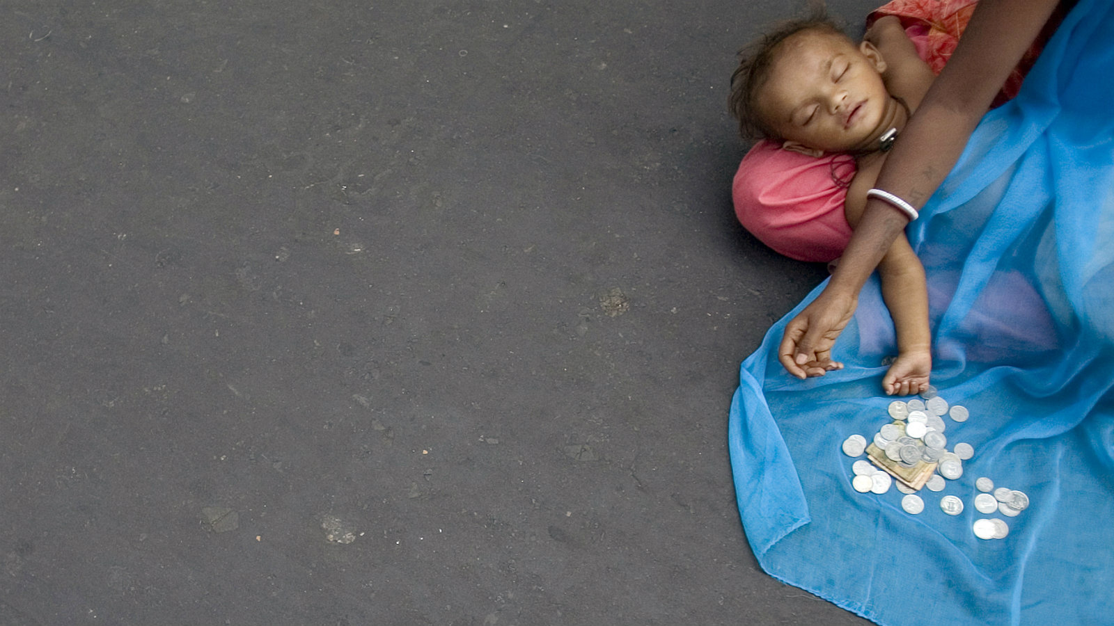 A child sleeps on the lap of a beggar in Kolkata.