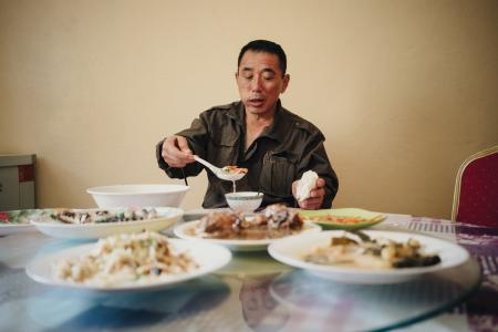 Liu Zhaoquan, who works in a fish meal factory in Nouadhibou, Mauritania, eats Chinese dishes from his native Shandong province in the factory canteen. Liu returns home only once every two years. The canteen food is one of the few reminders of home.