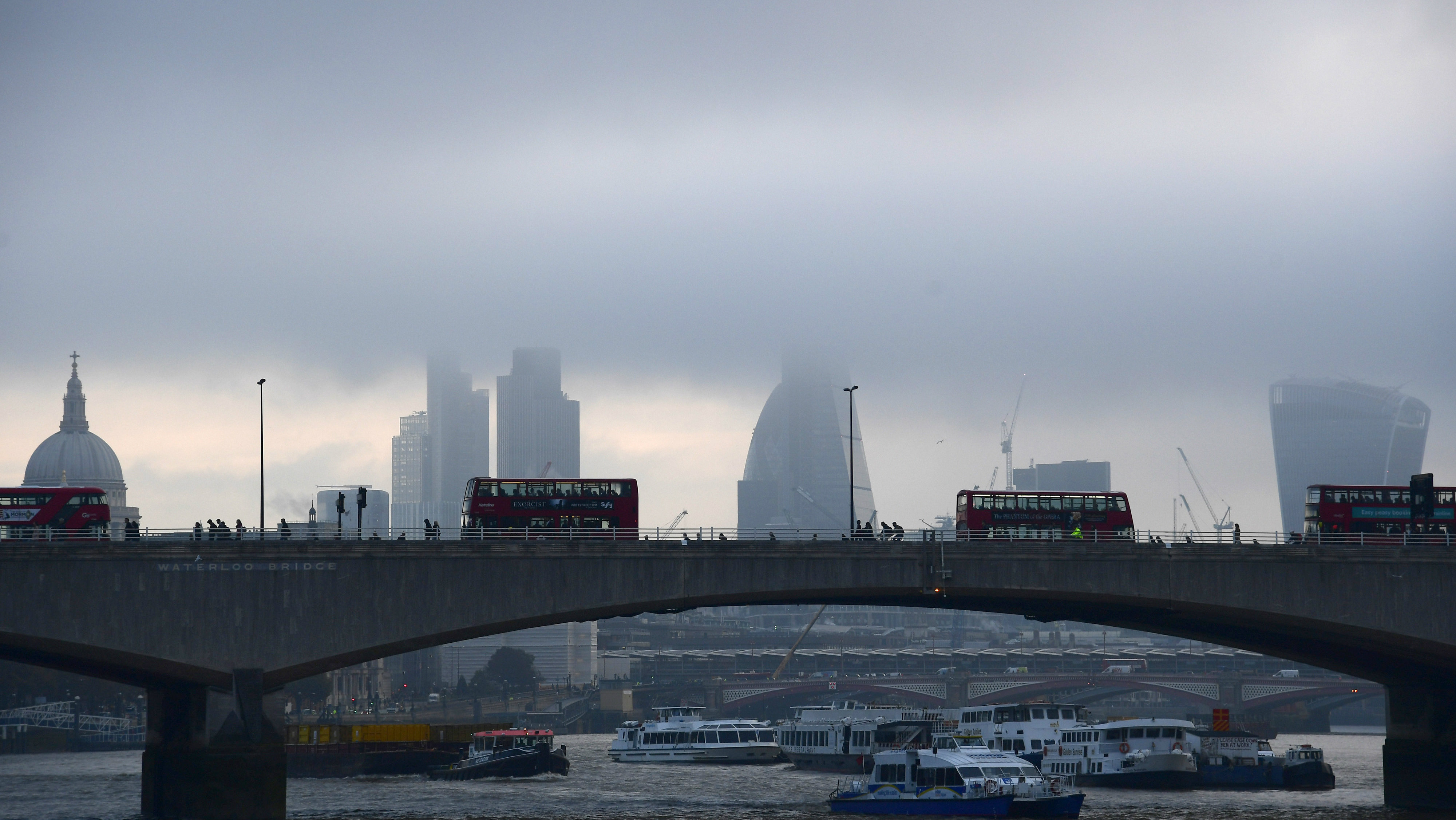 City workers cross the River Thames with the City of London financial district seen behind in London, in Britain October 27, 2016